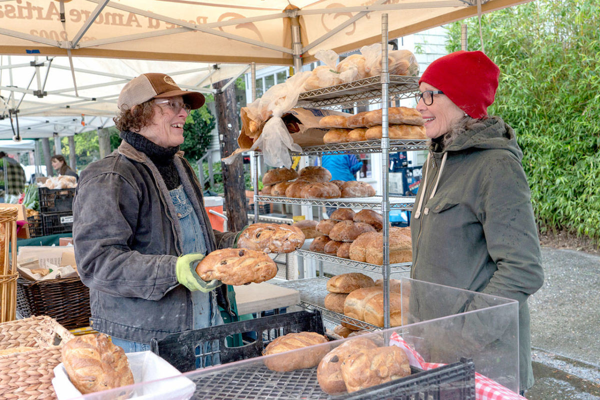 PORT TOWNSEND — Heather Hicks, left, and Linda Yakush, owner of Pane d'Amore bakery in uptown Port Townsend, prepare loaves of bread and sweet rolls for sale at the opening of the Port Townsend Farmers Market on Saturday.