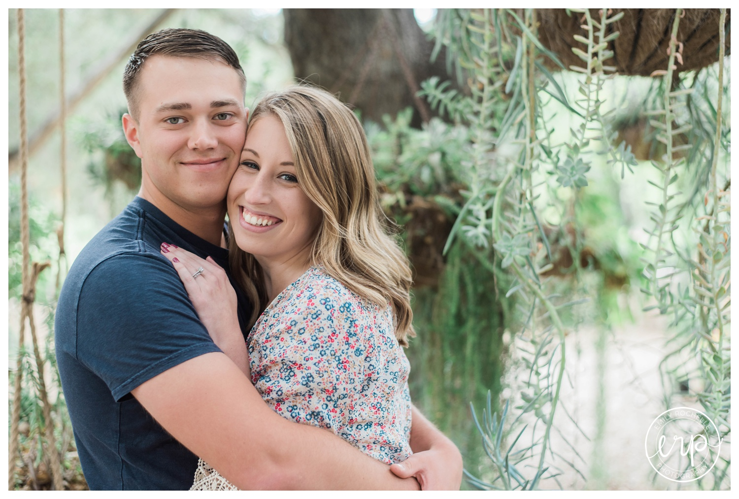 Couple during engagement session at Myrtle Creek smiling at the camera.