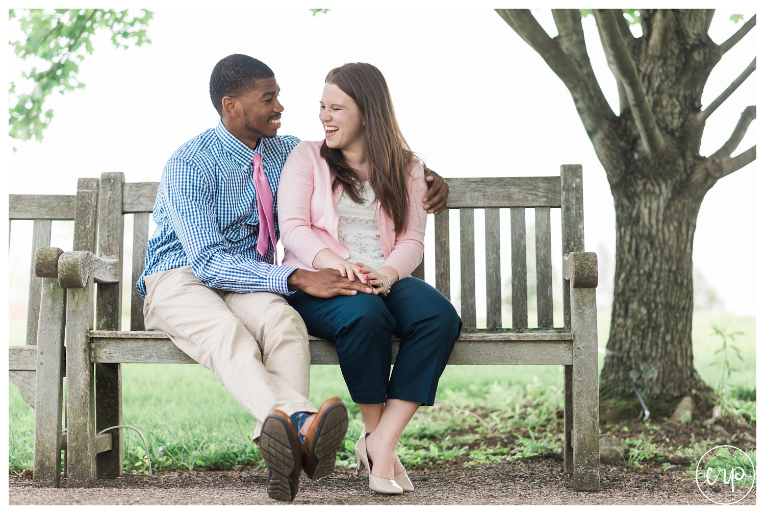 Couple sitting on a bench and laughing together.