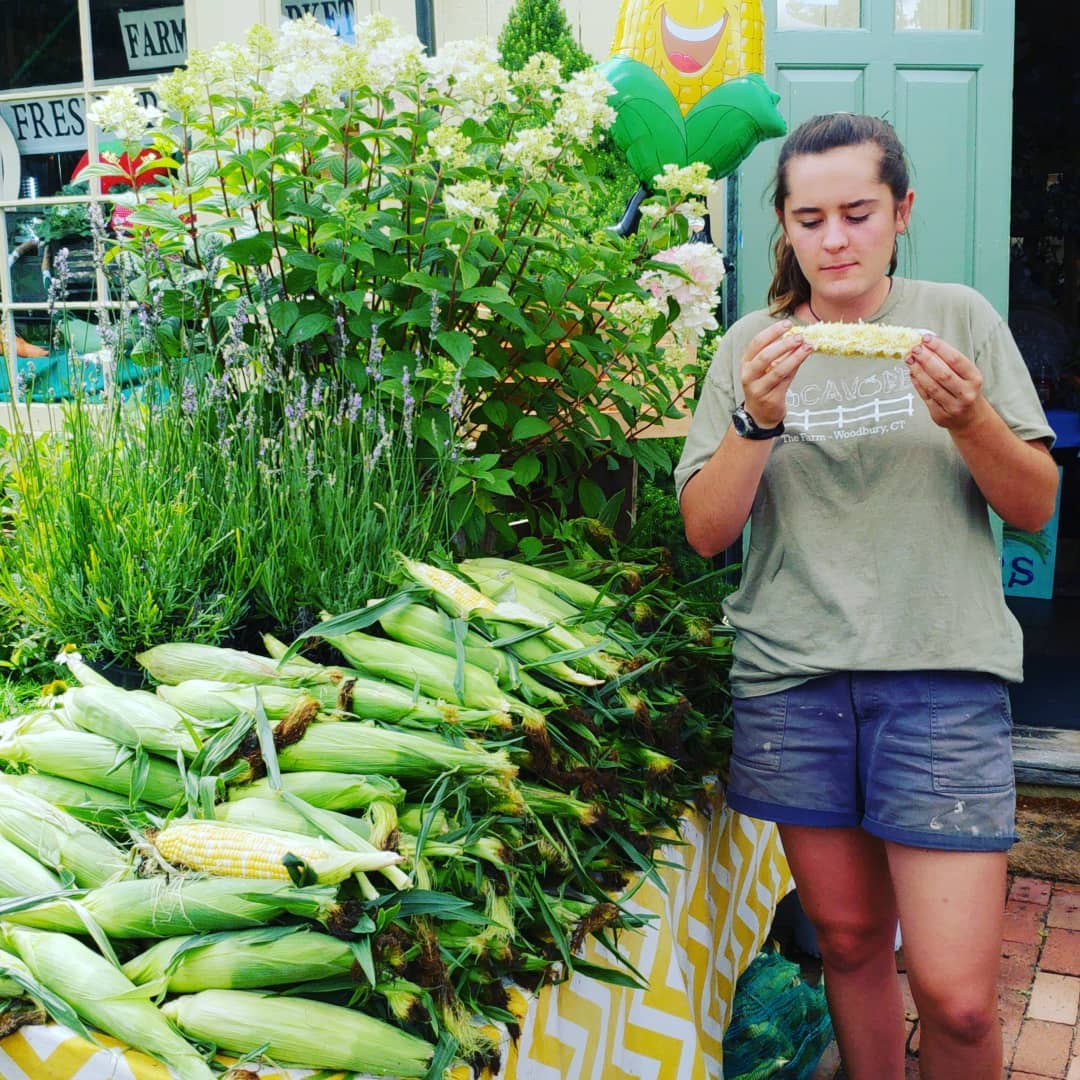 Claire taste testing The Farm's Famous Corn.  We like our farm-stand help know the flavor and quality of each offering.