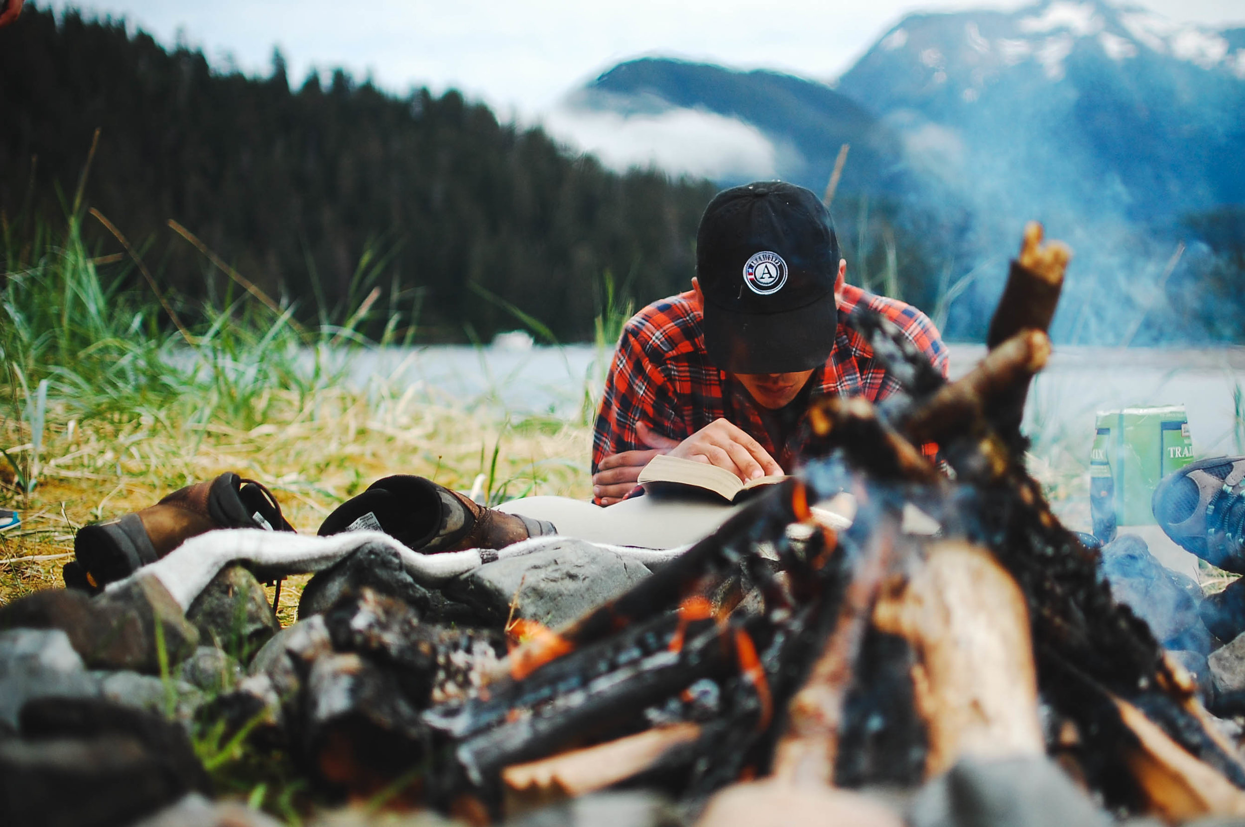 N. dries his shoes and reads by the fire while camping in southeast Alaska