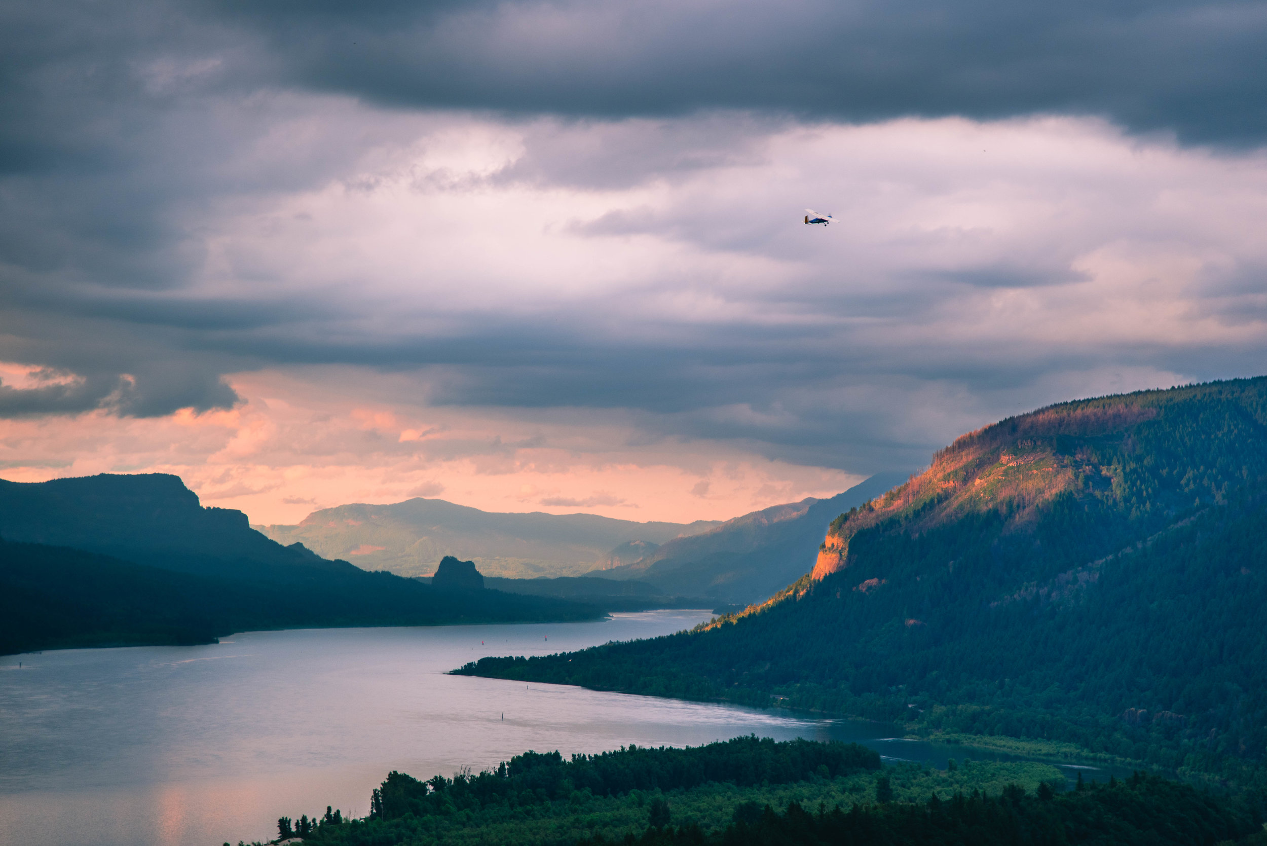 A small plane flies over the Columbia River Gorge at sunset