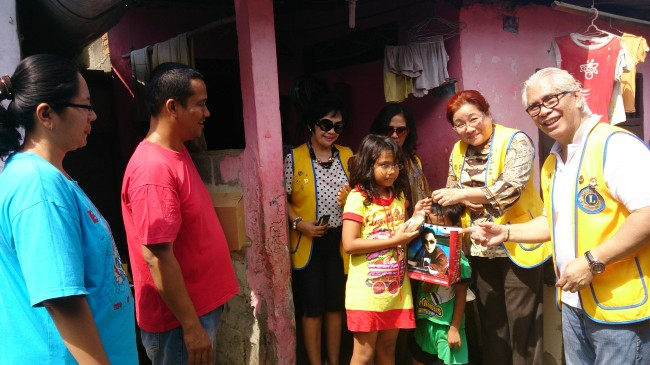 Mrs. Grace from Lions Club Jakarta Menteng presenting the eyeglasses to one of the children in Kampung Beting