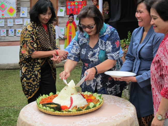 Ibu Anie Hashim Djojohadikusumo didampingi Ibu Tuti, Ibu Wiwied dan Ibu Tyas, memotong tumpeng peresmian Apotek Wiwied Farma dan PKm WADAH desa Cibodas, Lembang