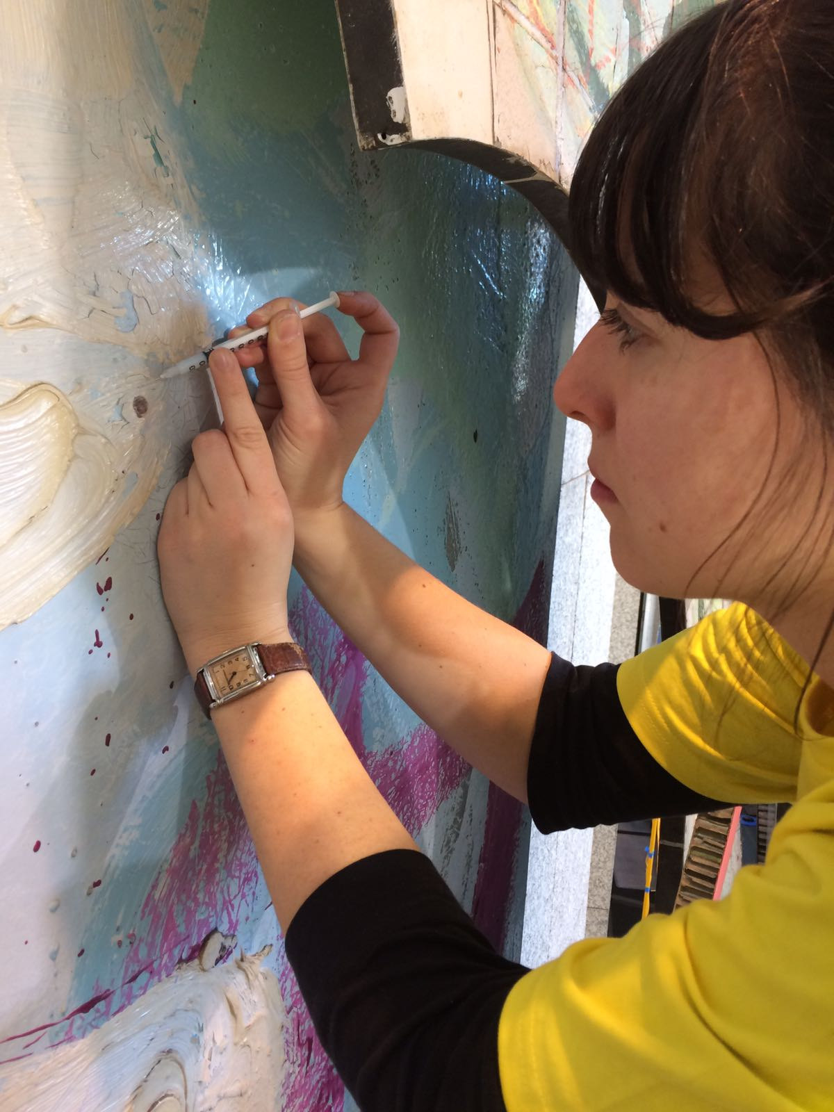 Consolidating flaking paint with a syringe
