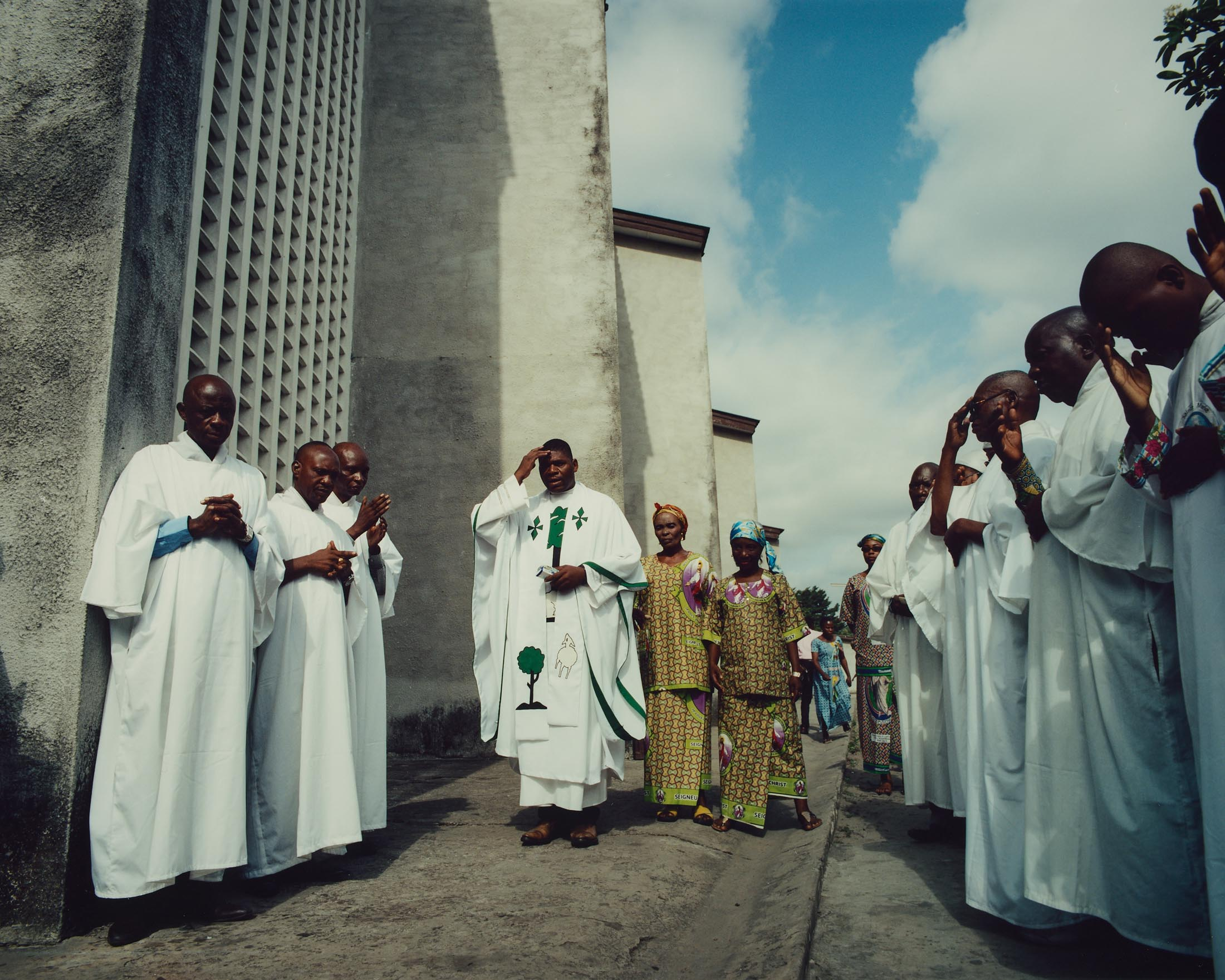 """Abbé Ponde leads a prayer after service at St. Augustin, Lemba, Kinshasa. """" We must see the social conditions of the population change. We need a peaceful life, without trouble. We want people to live freely""""."""
