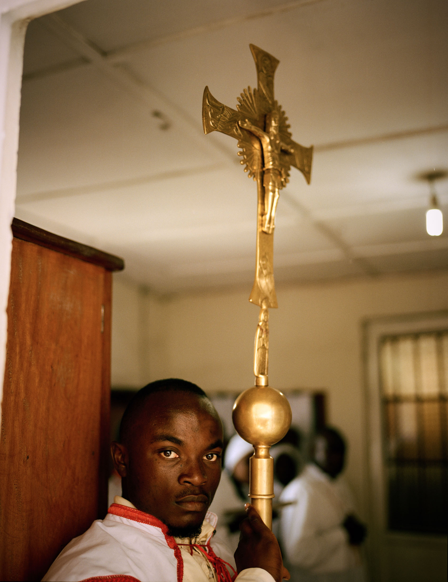 An acolyte waits with the ceremonial cross of the church of the Anuarite de Goma, North Kivu Province, Eastern DRC.