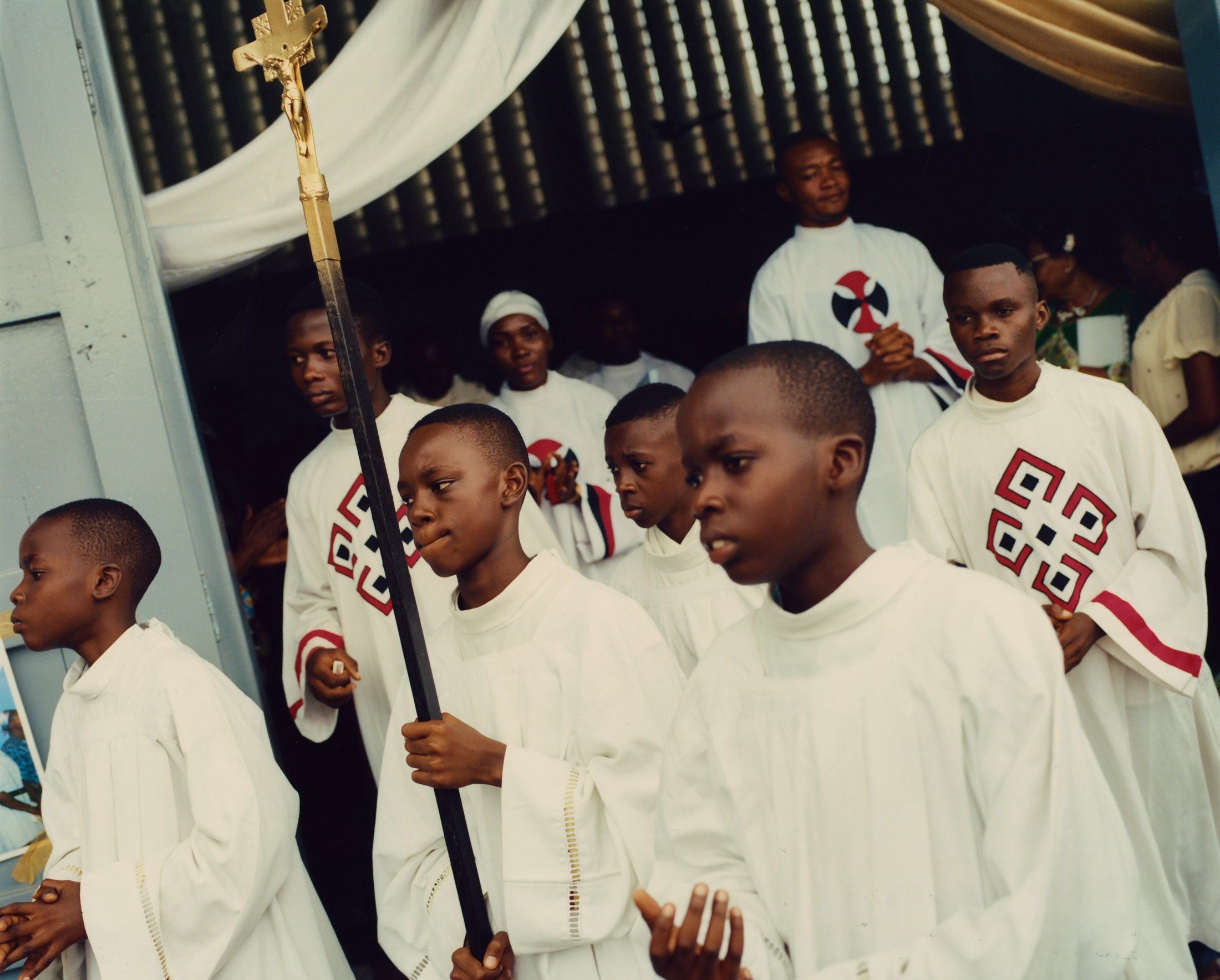 Between Sunday services, the acolytes of Saint Dominique walk the parish grounds. Limete, Kinshasa.