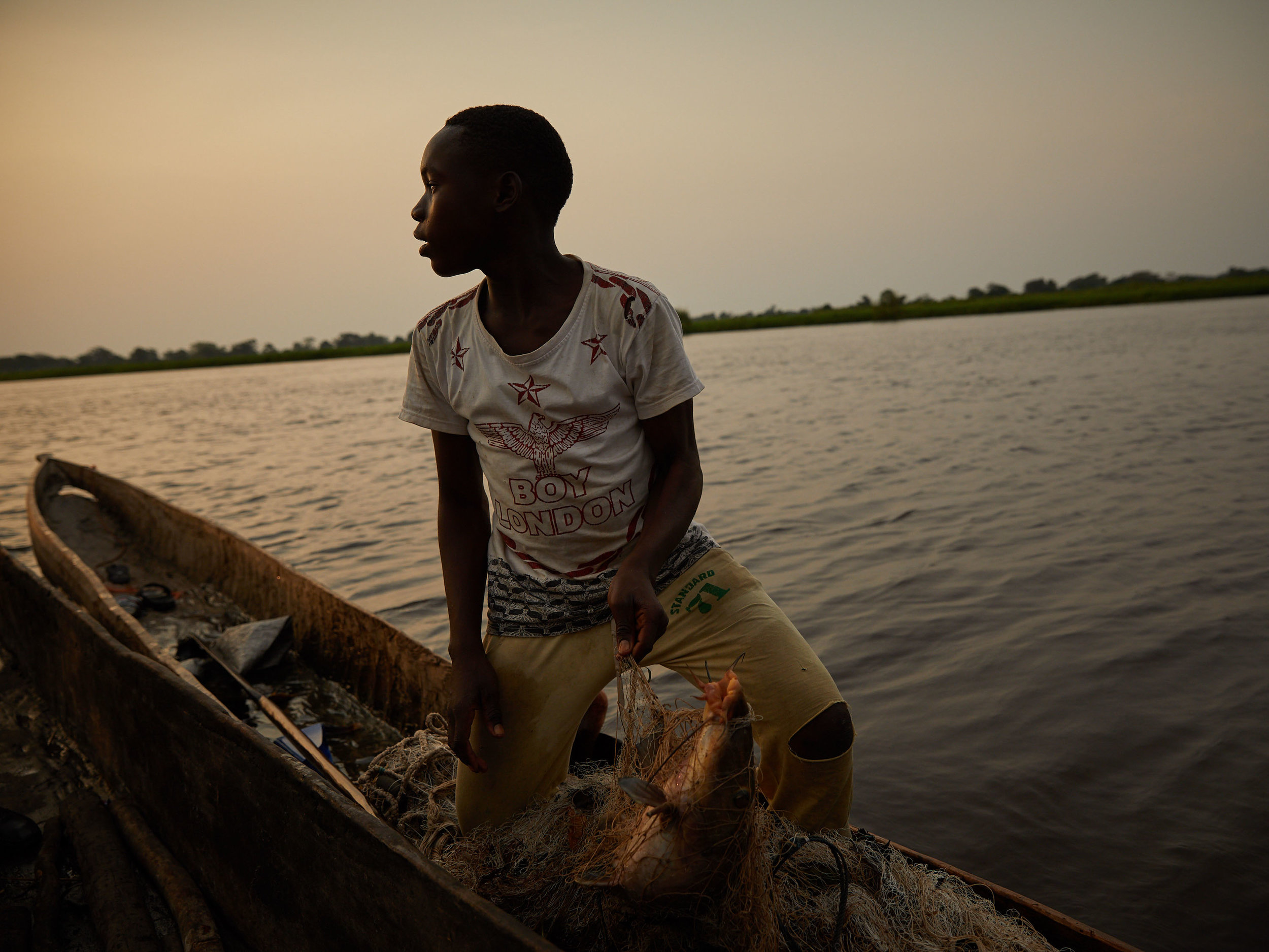 A boy sells his catch of the day mid-stream of the Congo River, Equateur Province. Venomous species of snakes pose a risk of bites when caught in nets or hunting along river banks.