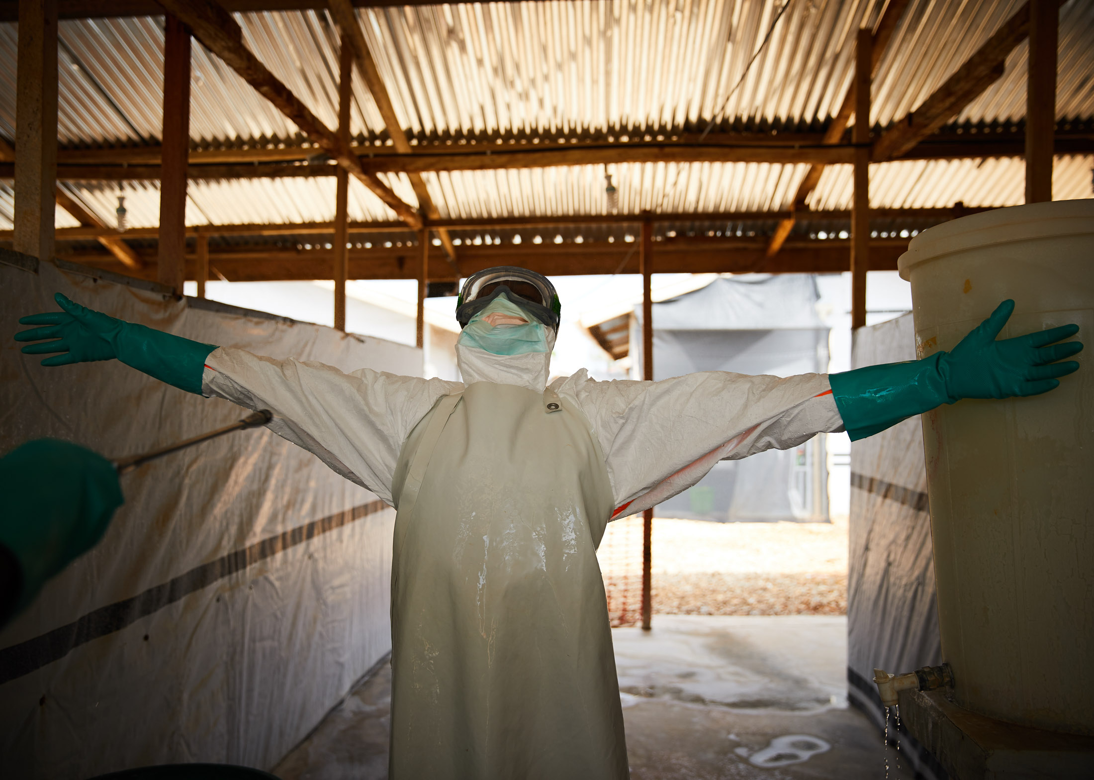 A health worker is sprayed with disinfectant after treating patients suspected of suffering from the Ebola virus at a transit health centre, Beni.
