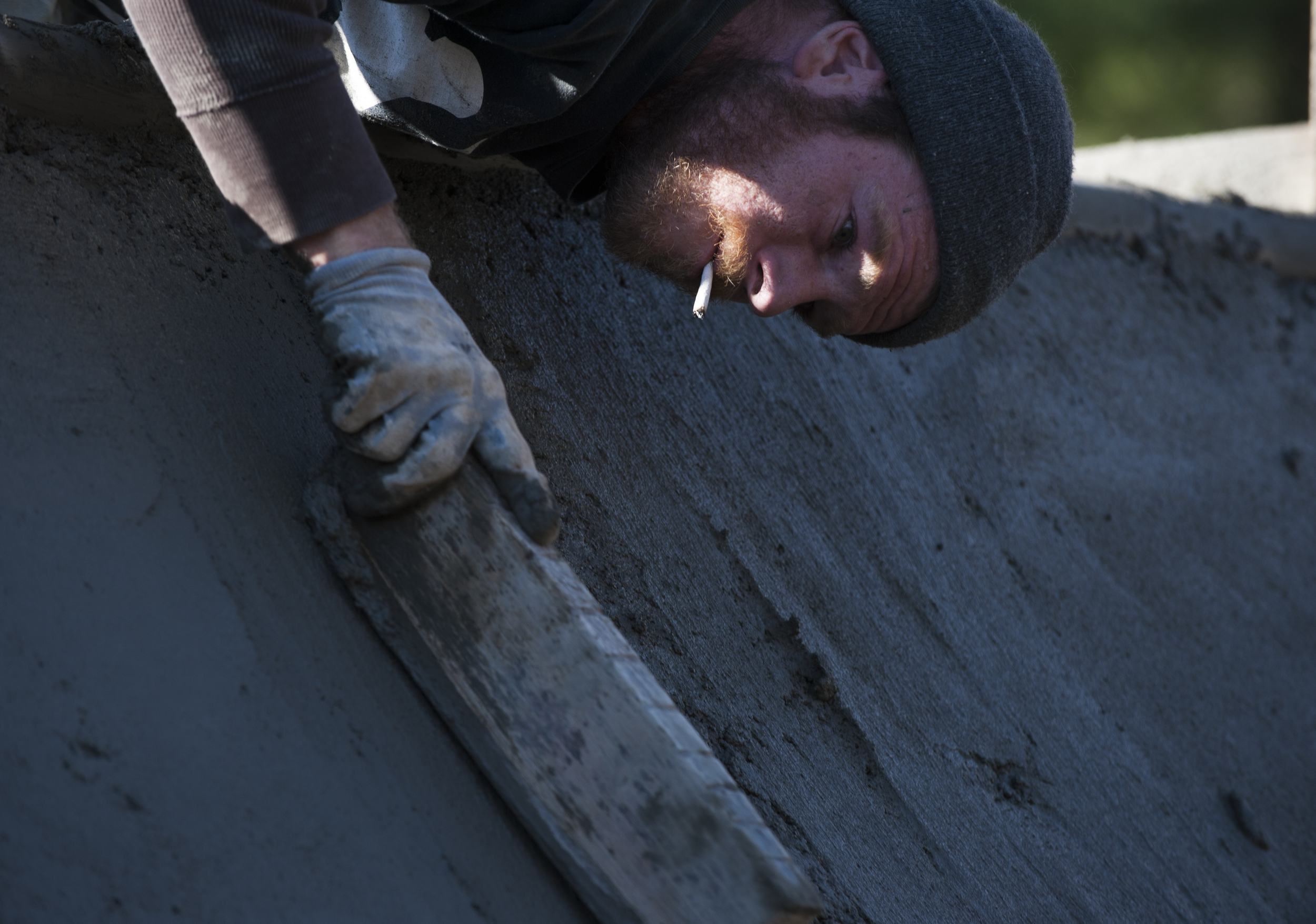 Zack Powell smooths out the concrete on one of the quarter pipes. Powell, a skateboarder, knows what to look for when finishing the concrete.