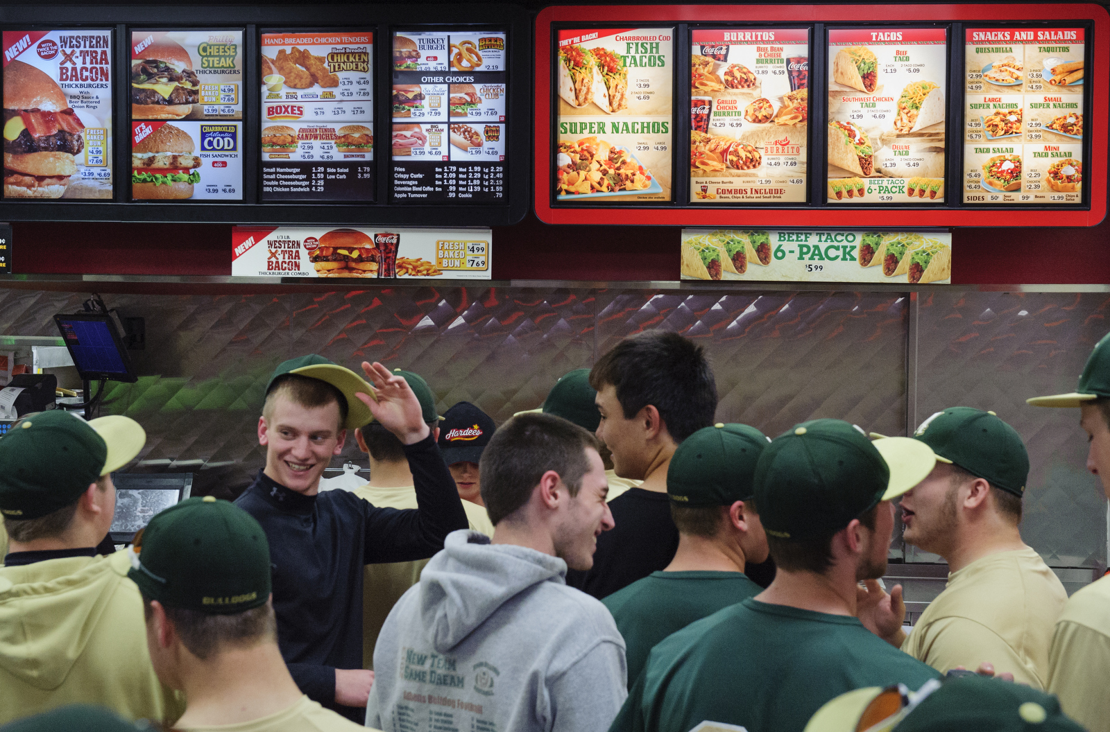 Hunter Mullins laughs with his teammates while they wait in line to order from Hardee's, a fast food restaurant. The team will usually go out to eat after an away game.