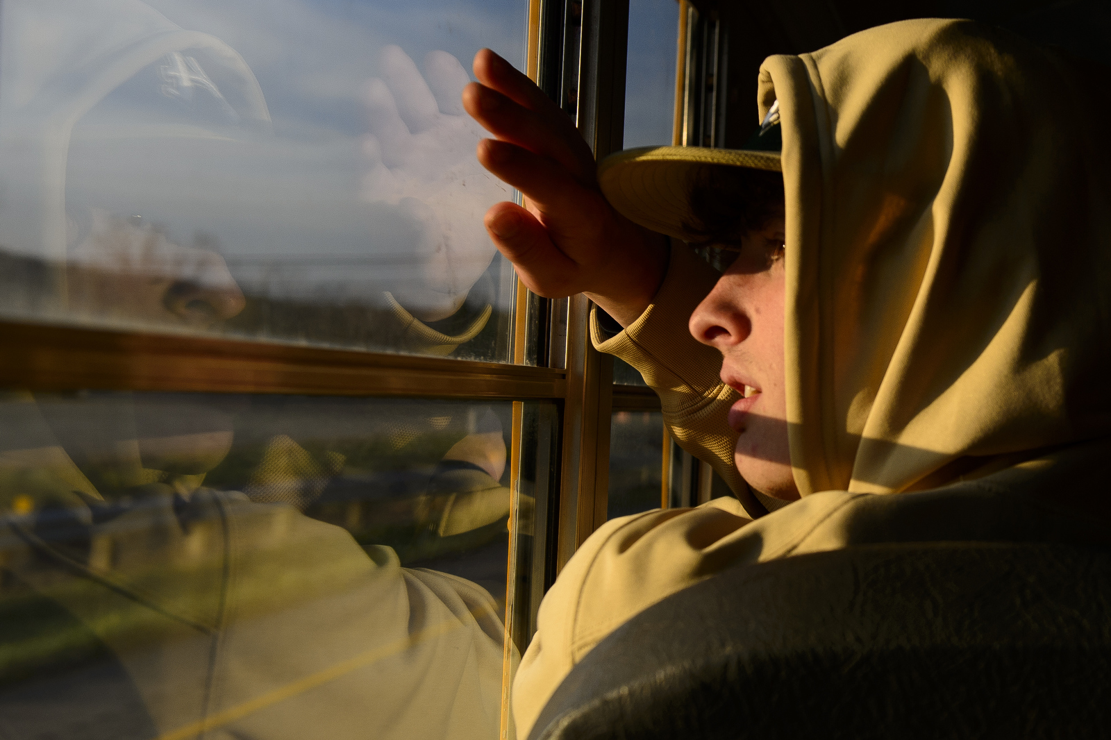 While the bus was passing Ohio University, Greysan Kerns looks out the window at campus and the sunset.