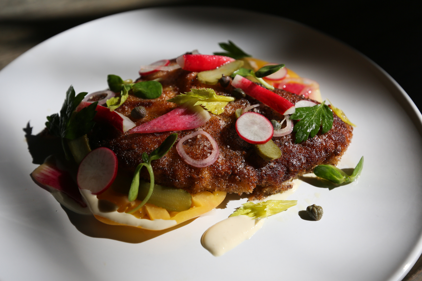 Cobia schnitzel with lemon emulsion topped with a tomato and radish salad at the Ordinary in Charleston, S.C.