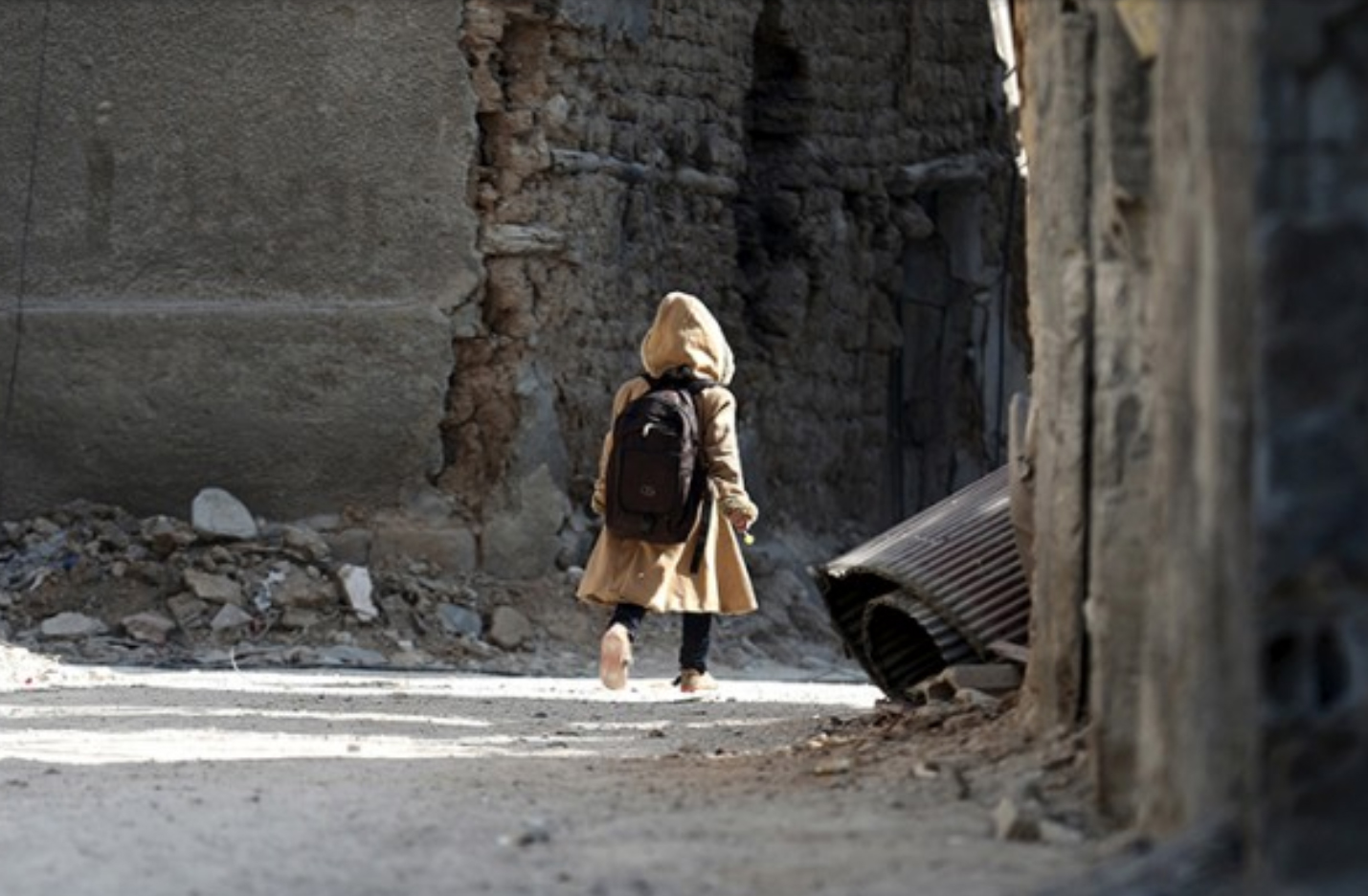 A child carries a school bag near damaged buildings in Harasta, in the eastern Damascus suburb of Ghouta, Syria January 30, 2016. REUTERS/Bassam Khabieh.