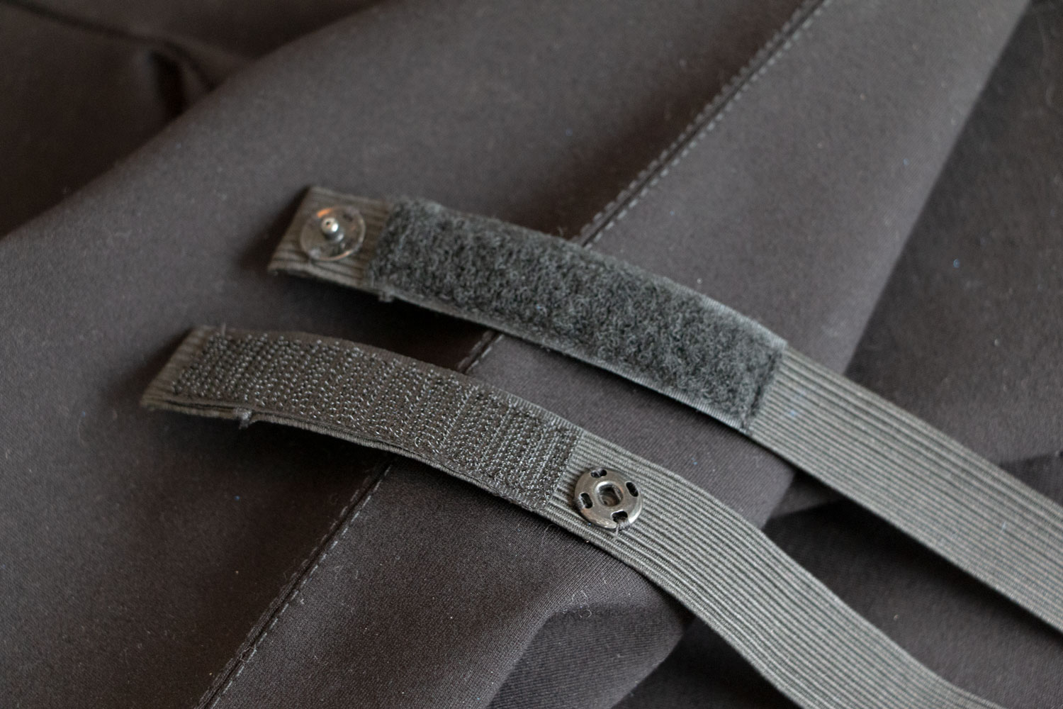 Single straps with snap to replace previous velcro and hook and eye closure. Old pants featured a single strap that would Velcro underneath with a hook and eye on top. Harder to come loose but harder for Jason to hook.