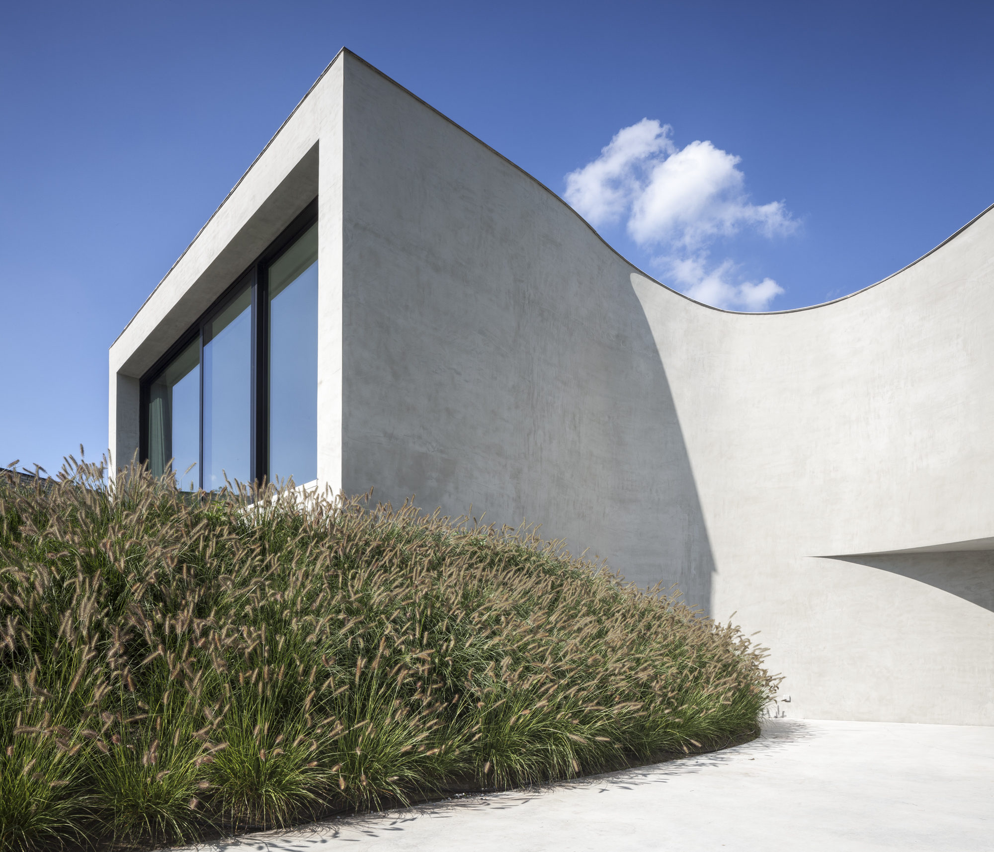 """Villa MQ , Tremelo Belgium   WINNER HÄUSER AWARDS 2017 - Spectacular Houses    """"On the outside, it captures modern art's essential look with its beautiful swirl of clean concrete. Its shape pulls you in and mesmerizes as it cuts through the sky smoothly. It appears to be sitting on its own pedestal, but in reality the building has many split-levels that cut into the ground. Aesthetically it resembles a monument to family life.""""  cfr. I love Belgium"""