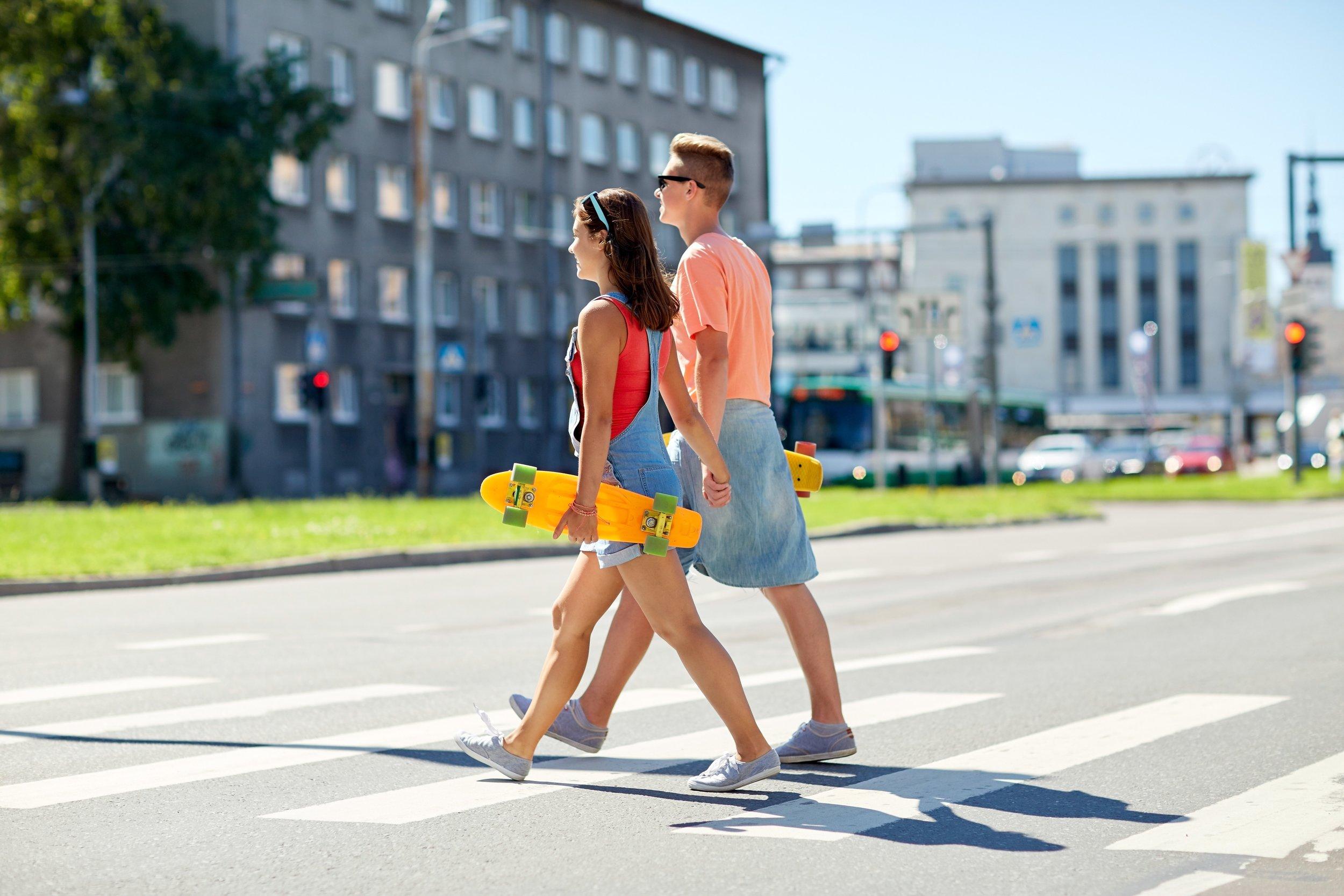 teenage-couple-with-skateboards-on-city-crosswalk-PK5XTU3.jpg