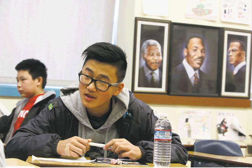 Photos by Lea Suzuki / The Chronicle   Freshman David Chen (right) sits next to portraits of Nelson Mandela, Martin Luther King Jr. and Malcolm X during ethnic studies class at Washington High School.