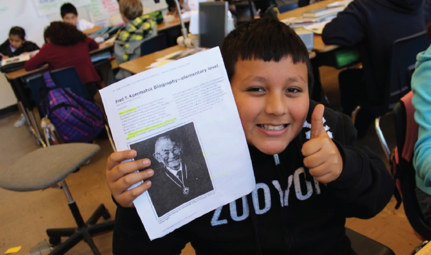 Student learning from a handout of the Teachers Guide