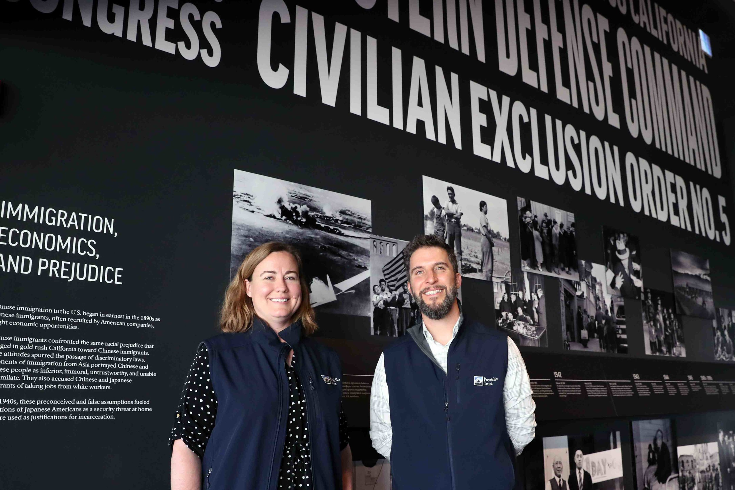 """Kathryn Inglin, Presidio associate director of external affairs, and Eric Blind of the Presidio Trust stand in front of one of the displays of the """"Exclusion"""" exhibit.  Photo by Darren Yamashita"""