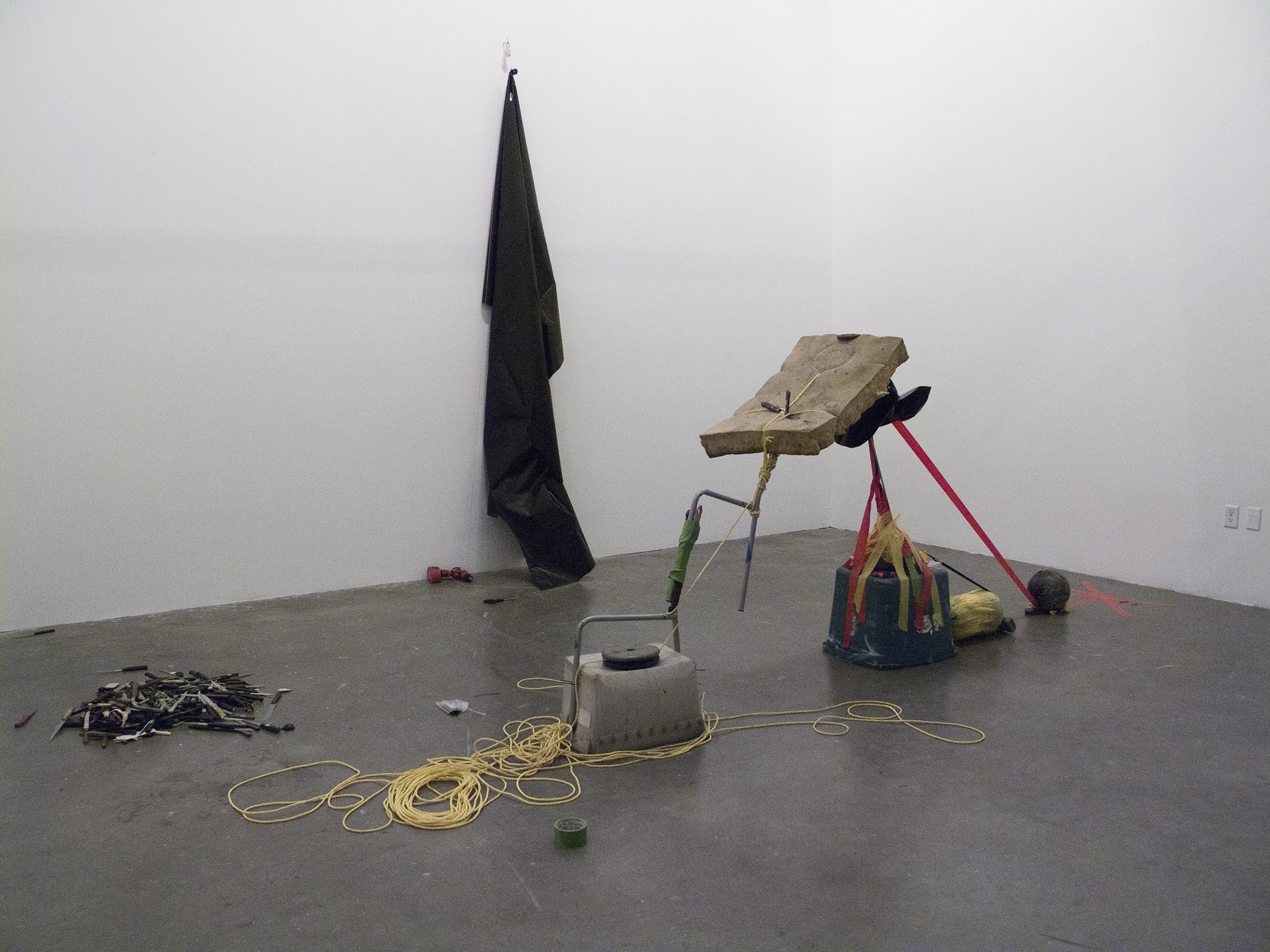 Two Teams Of Five Members Each, All Of Whom Are Blindfolded, Work To Build An Arch With Whatever Materials Are On Hand,  2012, Knives, nylon rope, duct tape, 2 barbell weights, 3 bowling balls, cordless drill, plastic curtain, couch cushion, zip ties   (click here for a larger image)