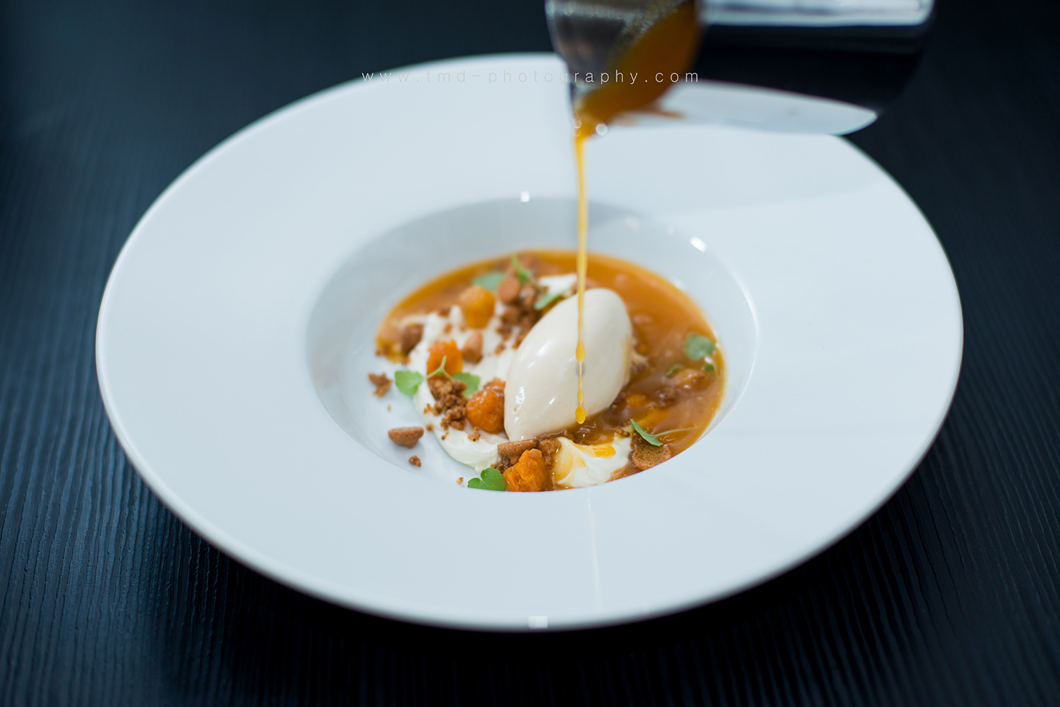 Dessert with cloudberries, caramel ice cream, almond biscuits and a hot cloudberrysoup