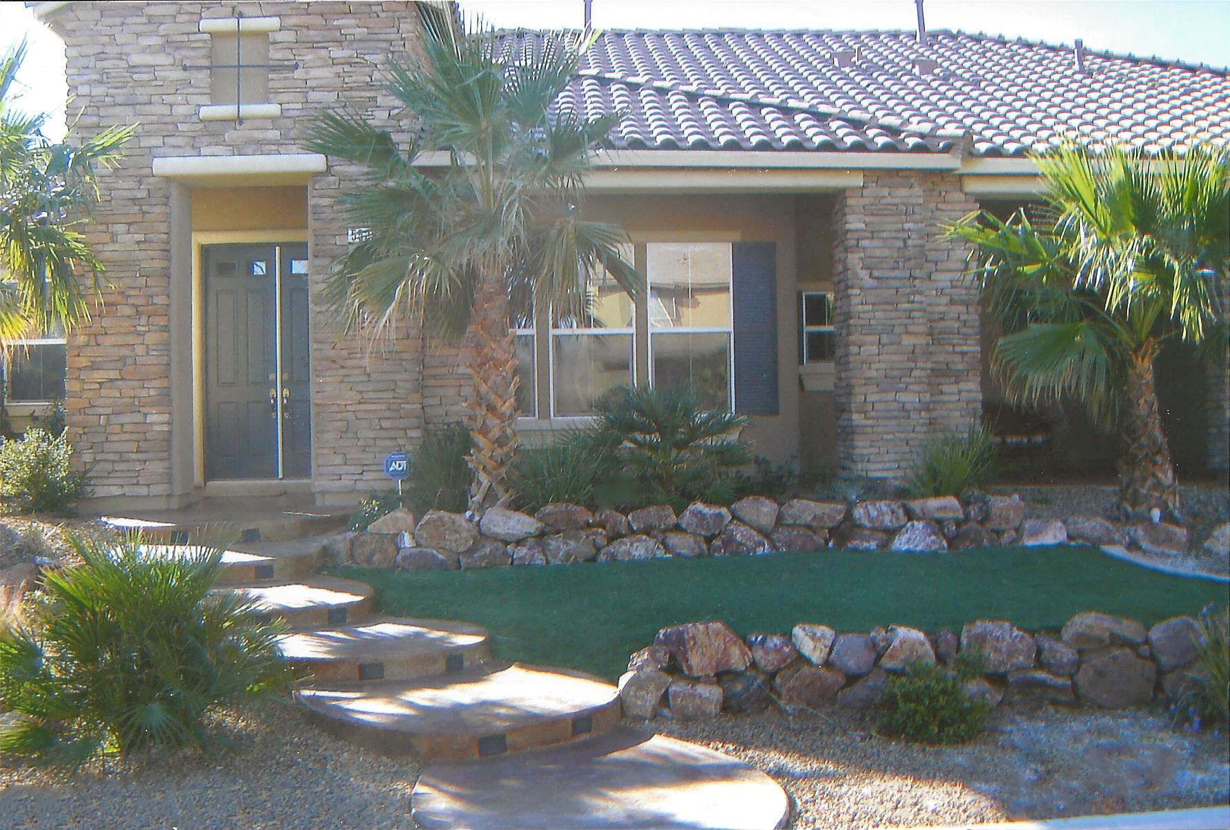 Front Yard Faux Turf Landscaping with Decorative Rock, Stained and Stamped Concrete Stairs, Palms and Plants.