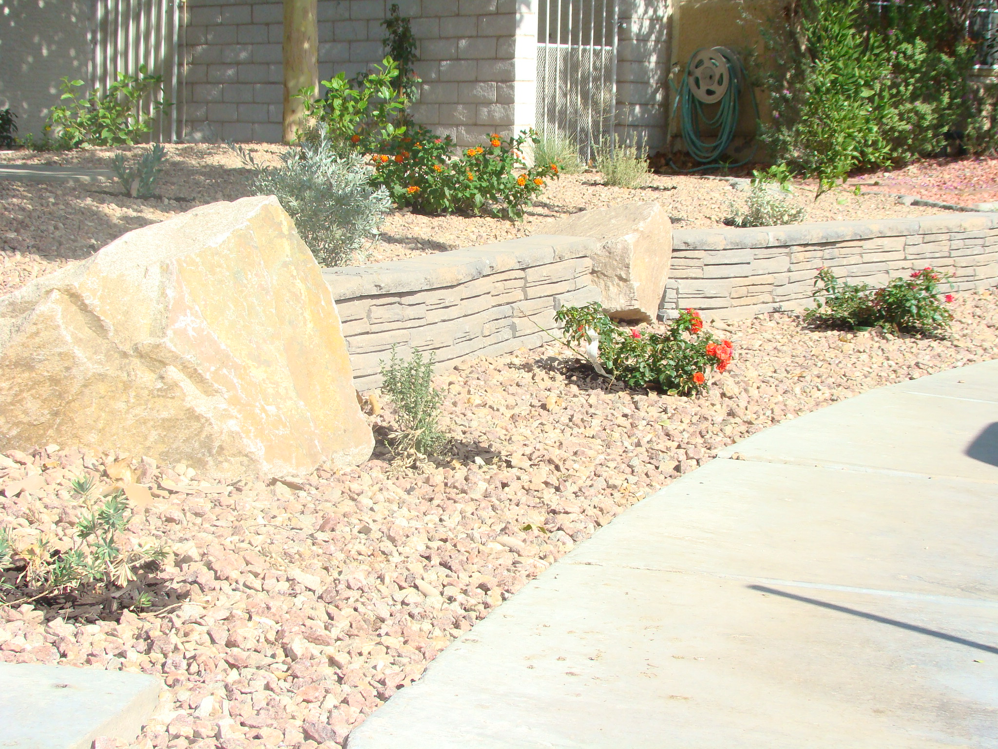 Desert Landscaping Complete with Decorative Rock, Stone Retaining Wall, Decorative Boulders and Low Maintenance Plants