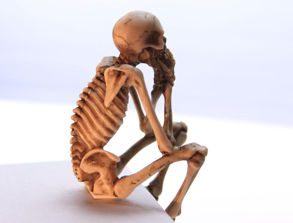 The all too common skeleton in a seated position.