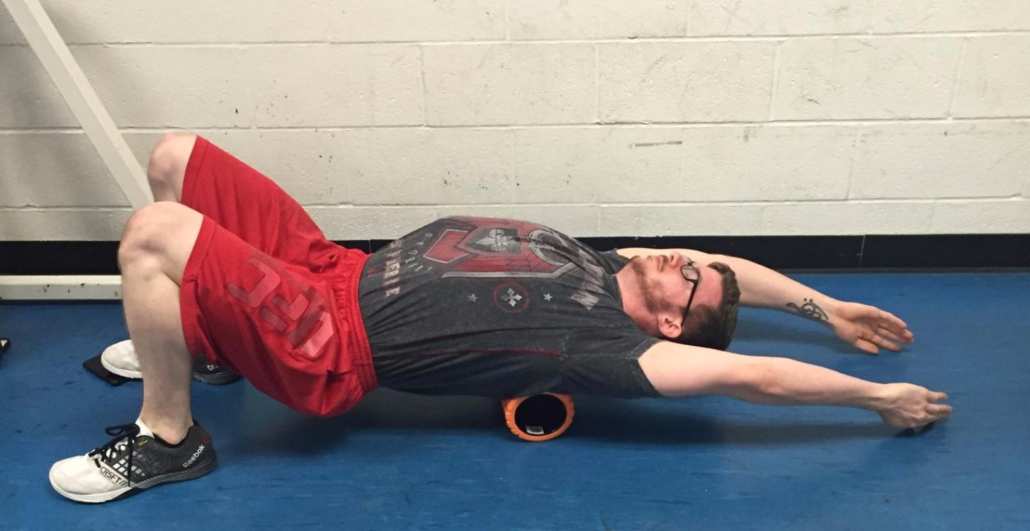 T-Spine Overhead Extension Smash - 5 minutes   Lay stomach up placing the foam roller in your mid back (or a stiff area of your upper back). Reaching overhead with your palms facing each other, raise your hips to keep yourself in a straight line. Keeping your core engaged, slowly lower your hips and force your hands down to the ground.