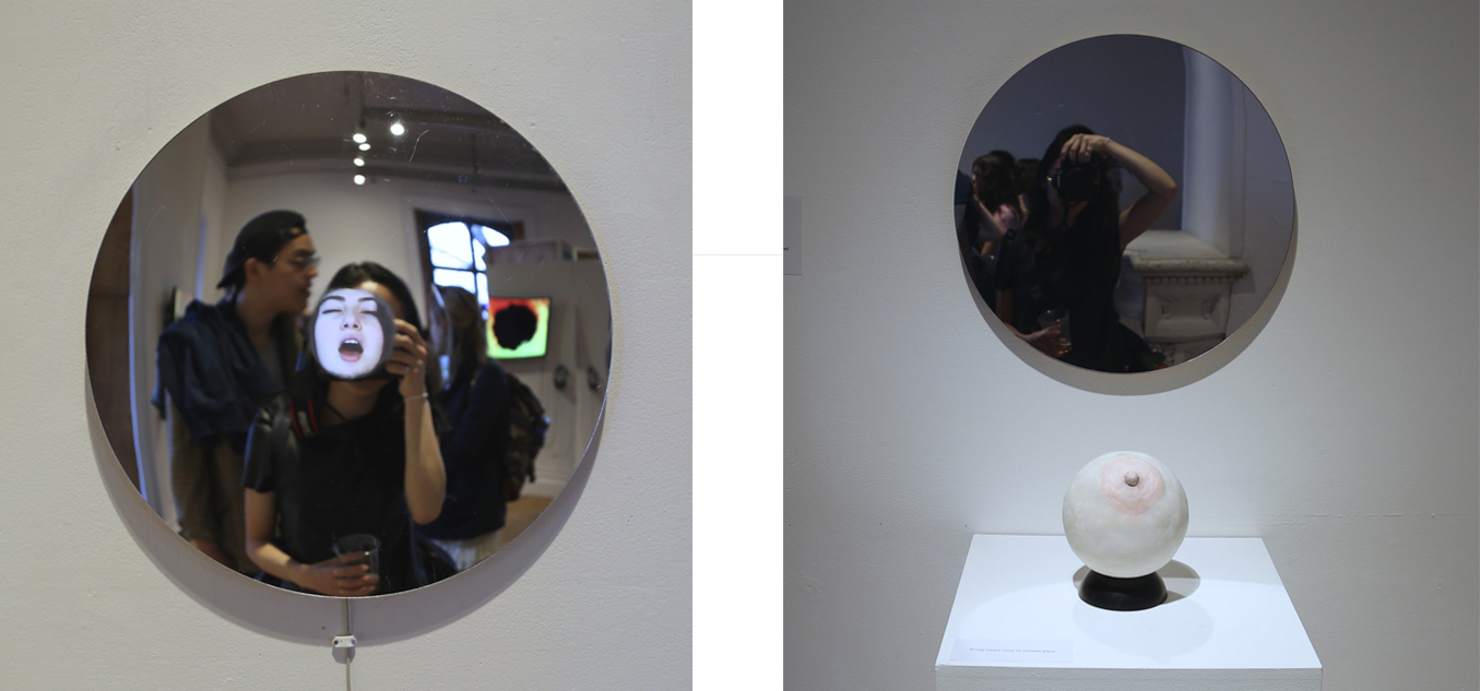 """Tit Me  consists of two circular shaped mirrors that are installed at eye-level for viewers to look at reflections of their face. One mirror plays a looping silent video of a female,  weed_slut_420 , performing an orgasm.  weed_slut_420  is a camgirl; a girl or a woman who poses for the webcam. The word is used for women who earn money by broadcasting, entertaining, and performing on webcams either from homes or studios.Viewers are able to see their reaction whilst watching this exaggerated orgasm, or either experience having  weed_slut_420 's face replaced onto their bodies.   The other mirror is plain, existing with a boob shaped coin bank. When viewers insert coins into the boob bank, an audio plays, """"HE SCORES!"""" Followed by sounds of cheering and applauds."""