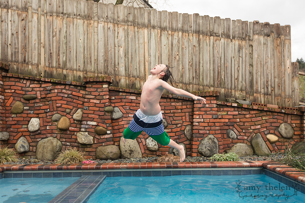 boy wildly jumping in pool