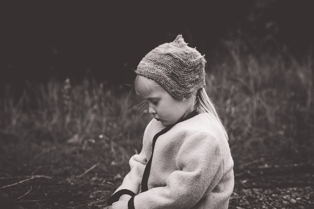 young girl sitting woods