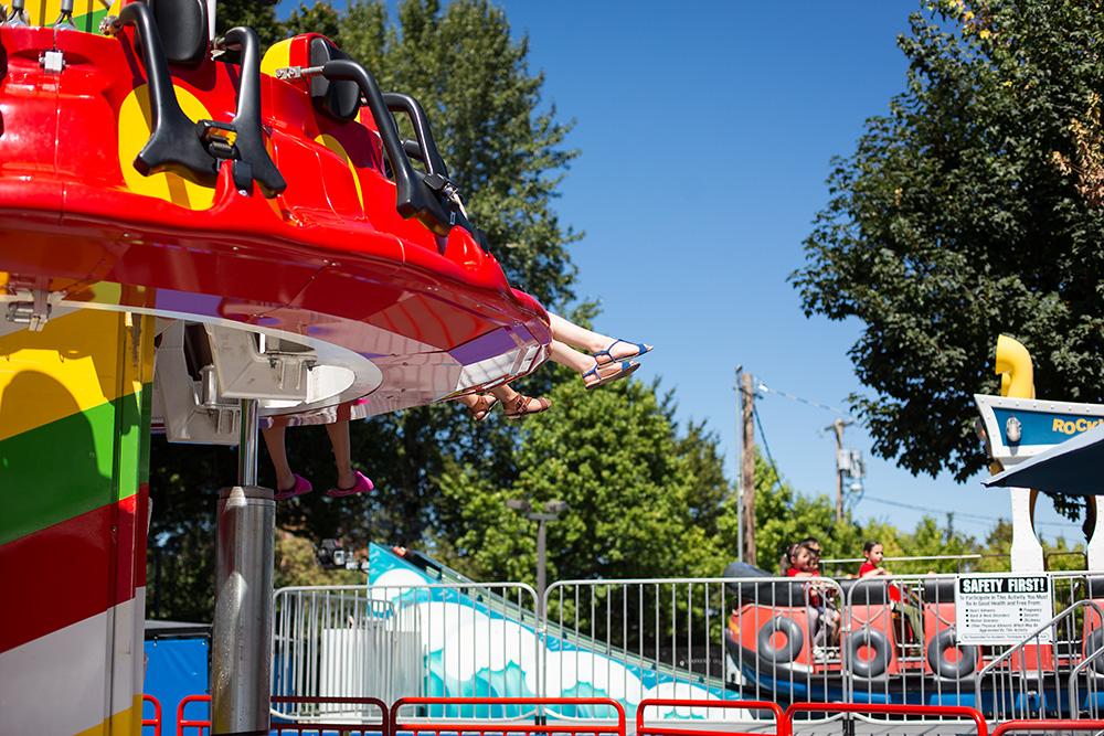 child on amusement park ride with blue sandals