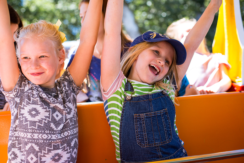 two girls with hands in air riding a tugboat at Oaks Park