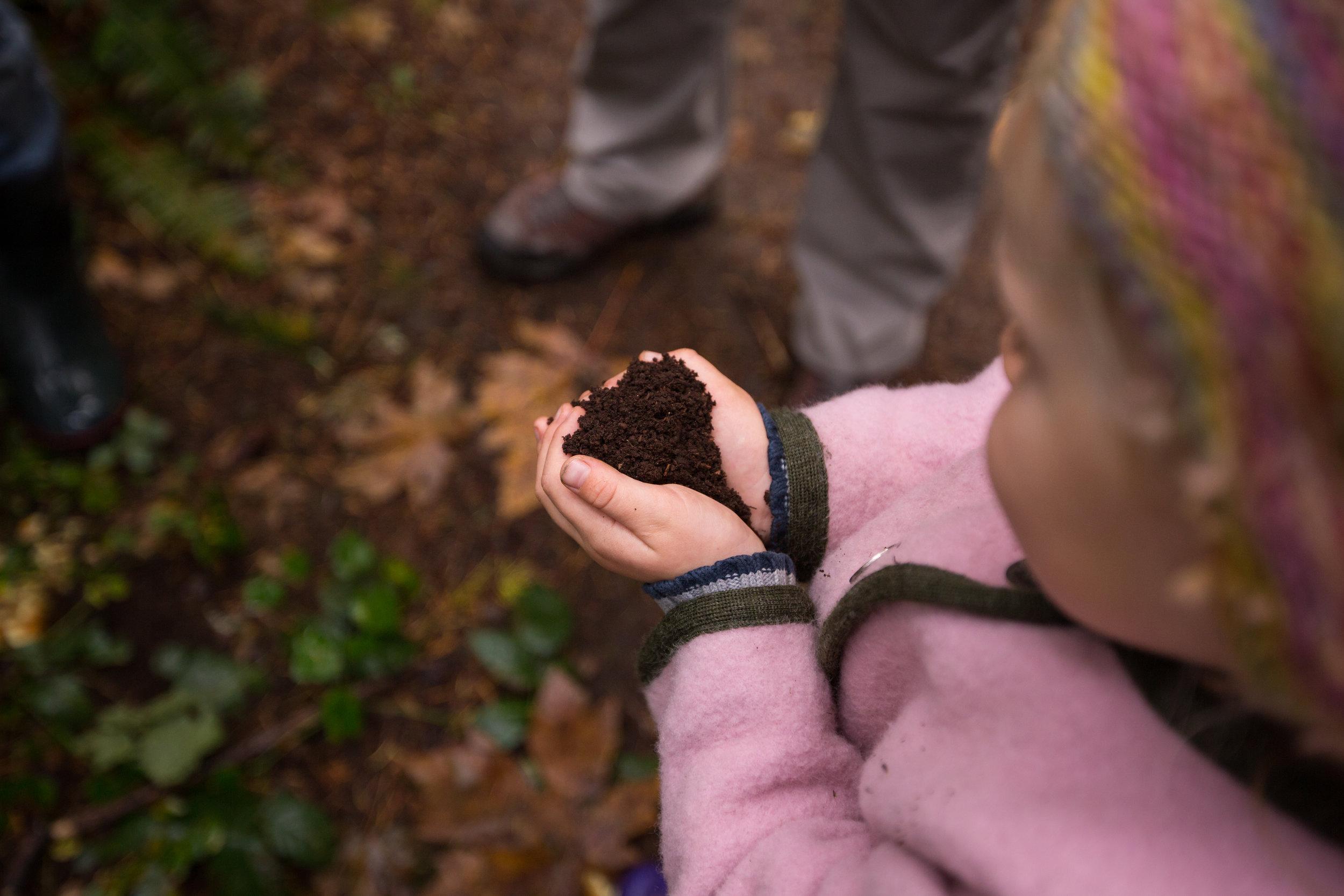 girl holding handful of dirt in shape of heart