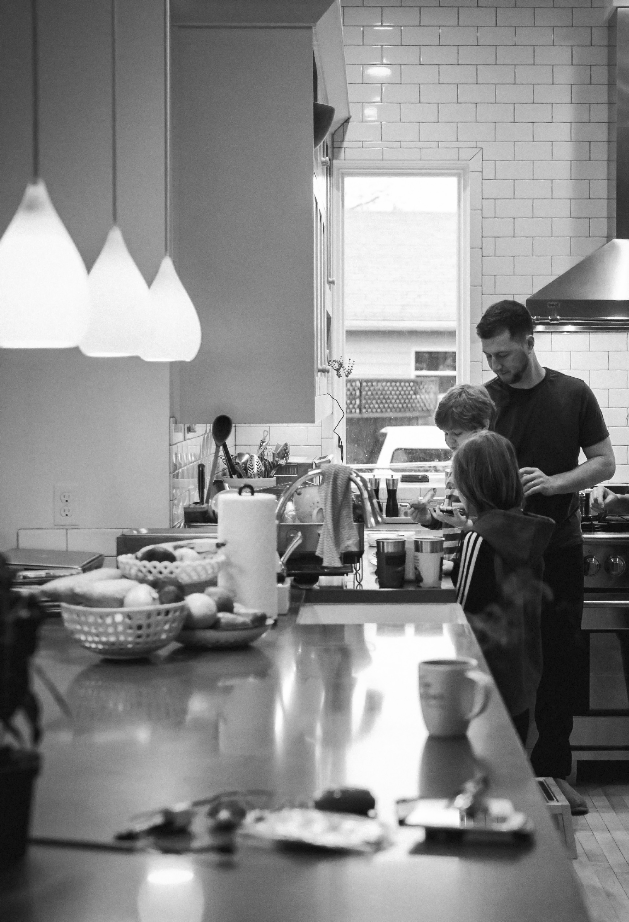 father and kids cooking in kitchen