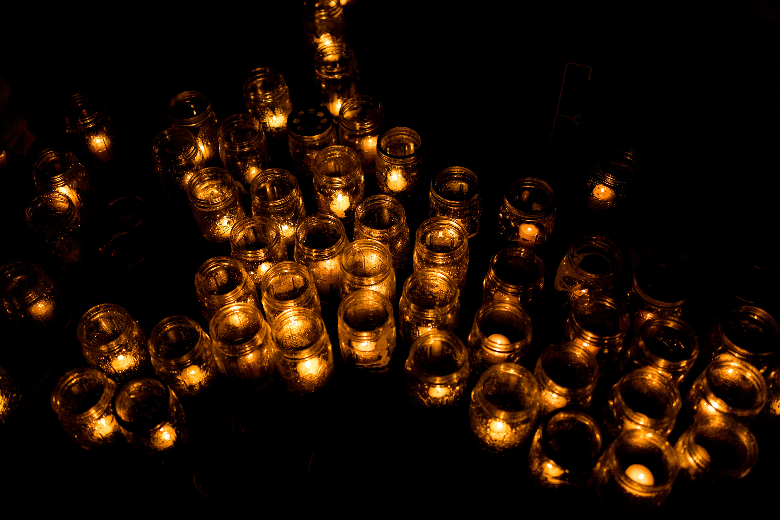 many glass jars lit by candles