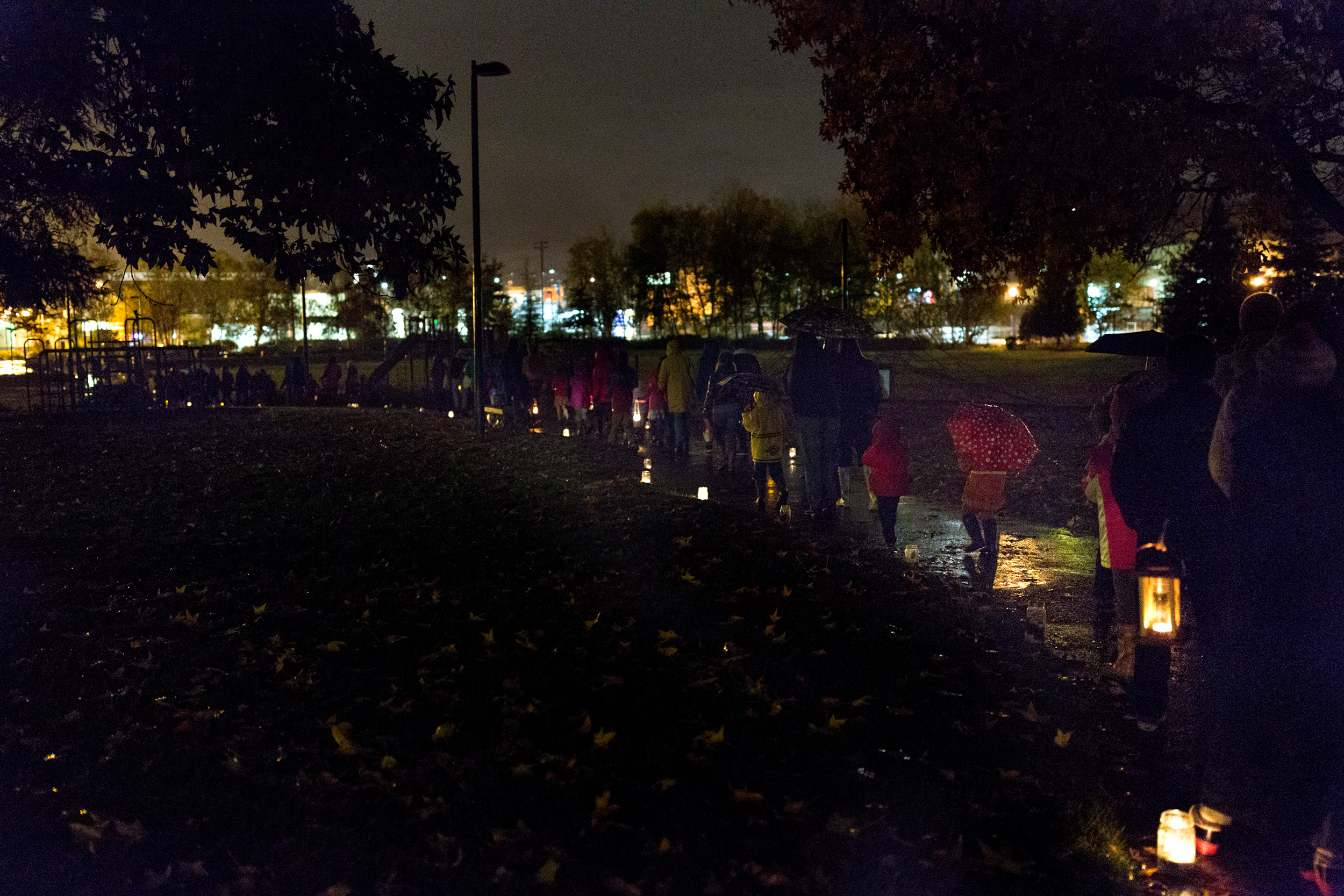 parents and children walking on path with lanterns