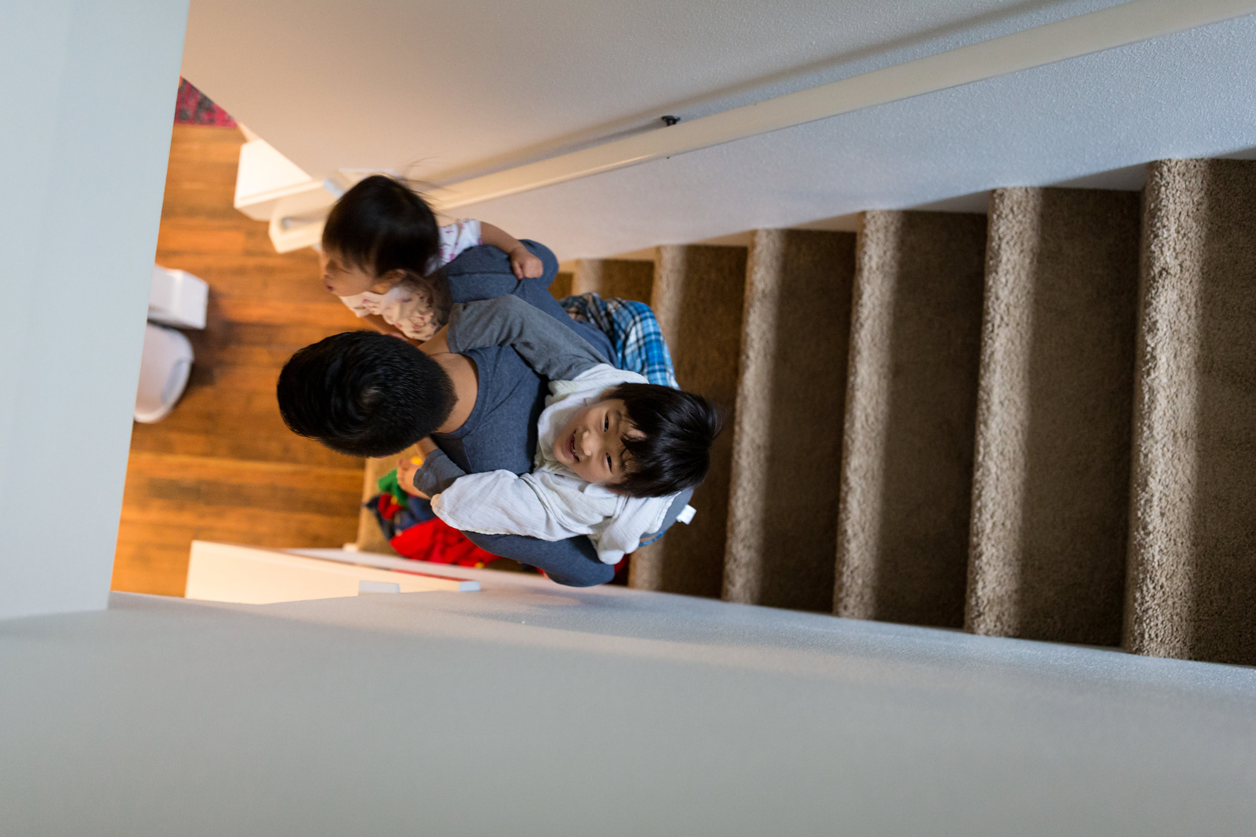 dad walking down stairs holding two kids