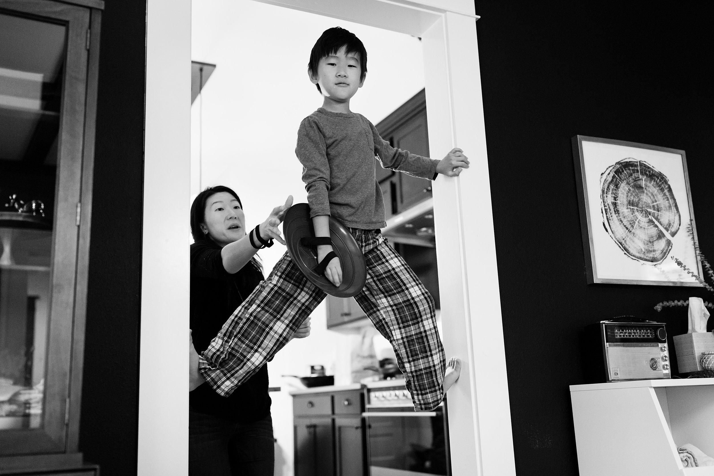 boy suspending in door frame while mom looks on