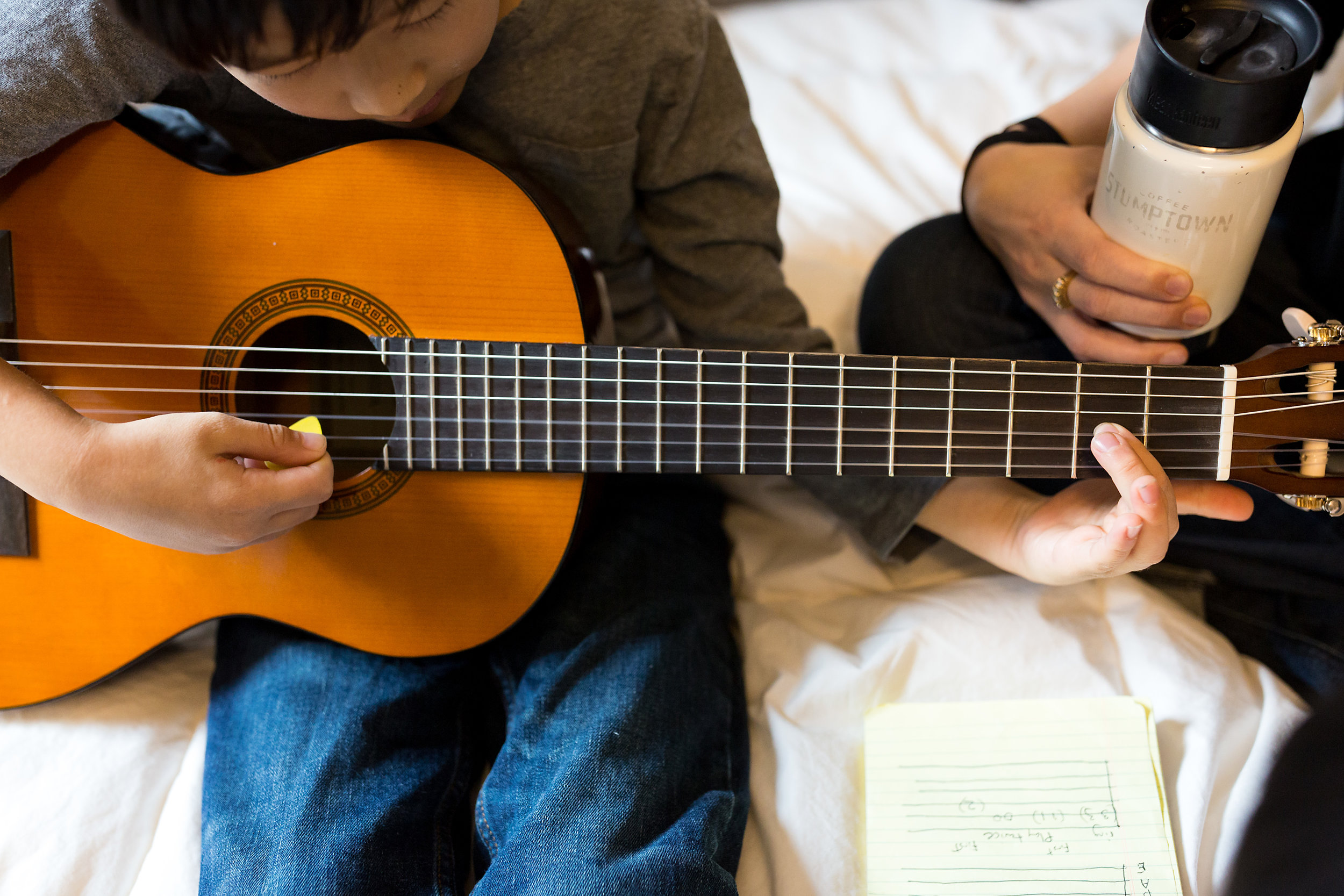 boy learning how to play guitar mom sits with coffee