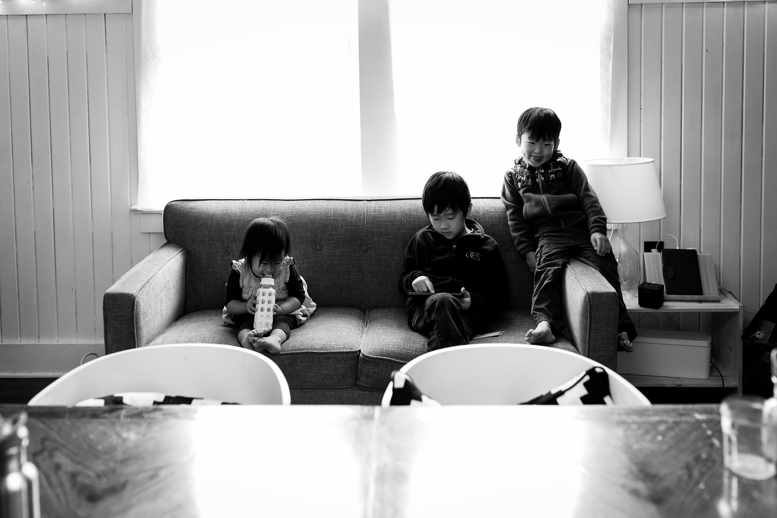 girl drinking from bottle, boy playing on iPad, other boy smiling