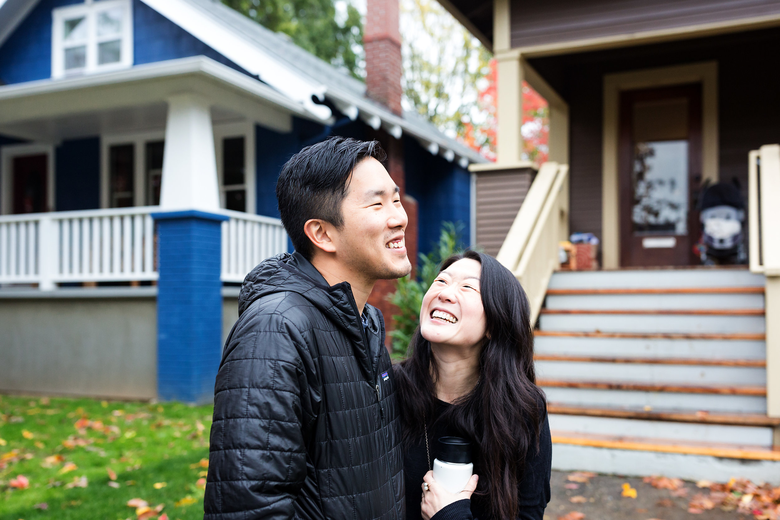 man and woman hugging and laughing outside home