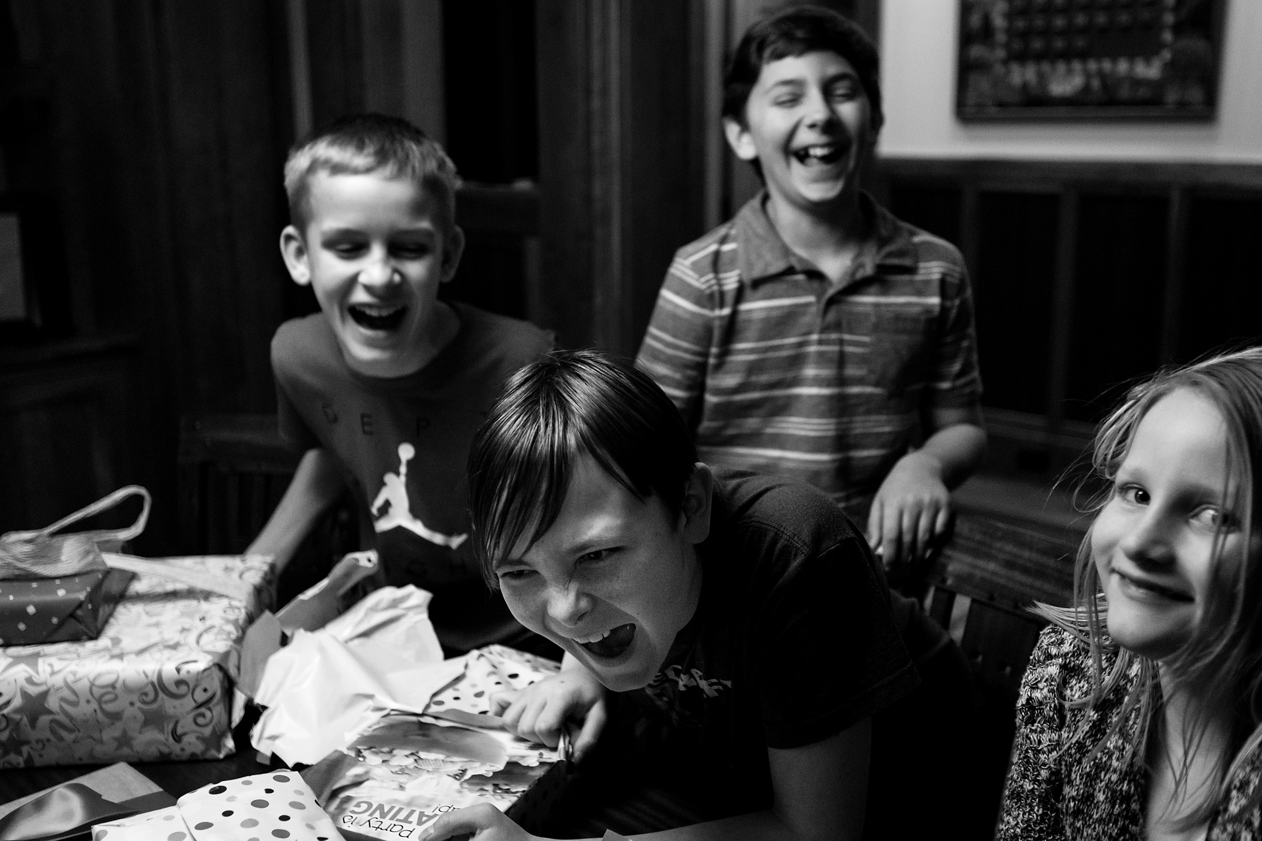 boy laughs hard with friends surrounding him Portland, OR