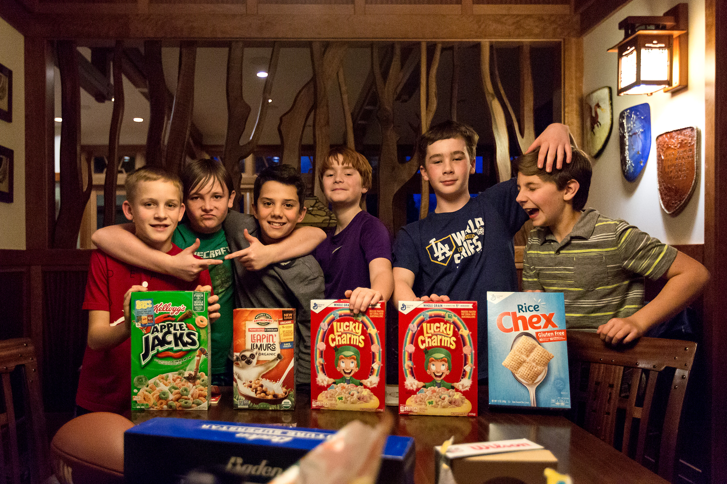 group of 6 tween boys stand with 5 boxes of cereal gifted as a gag gift