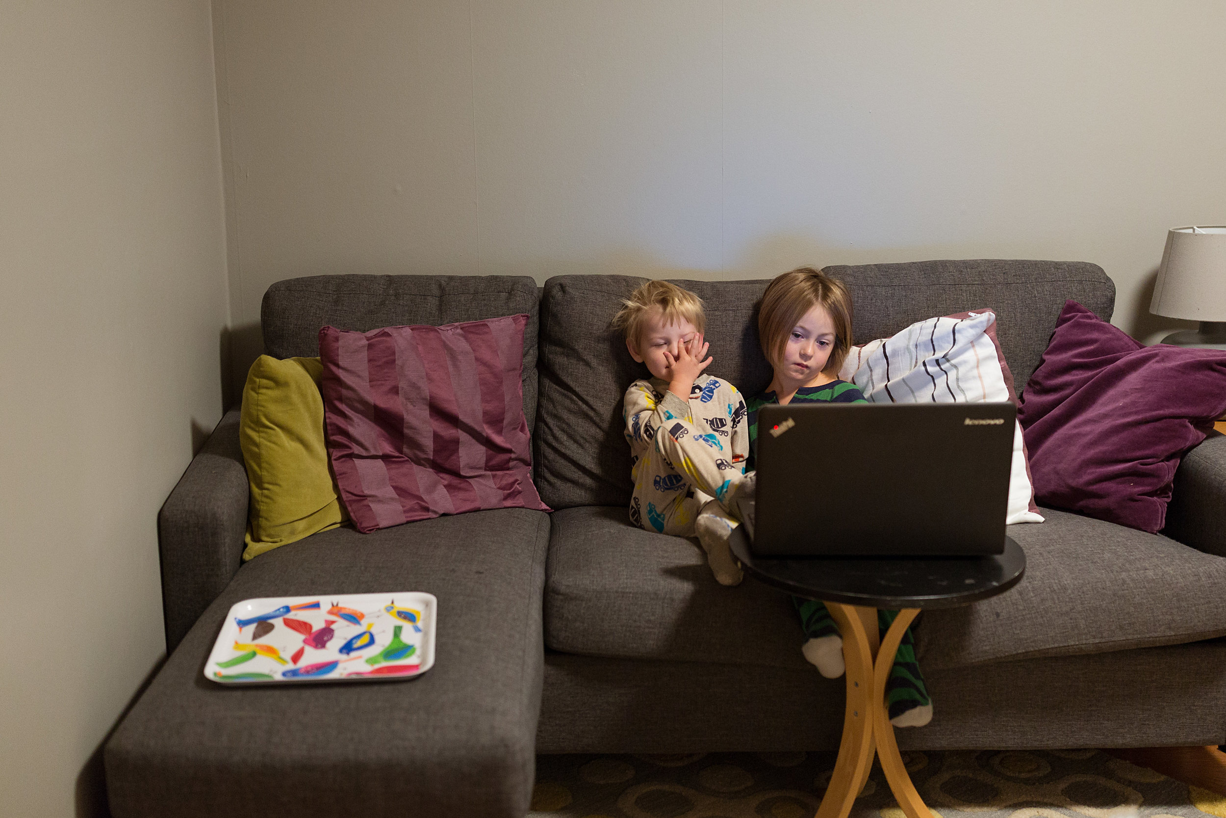 boy and girl sitting on couch watching laptop