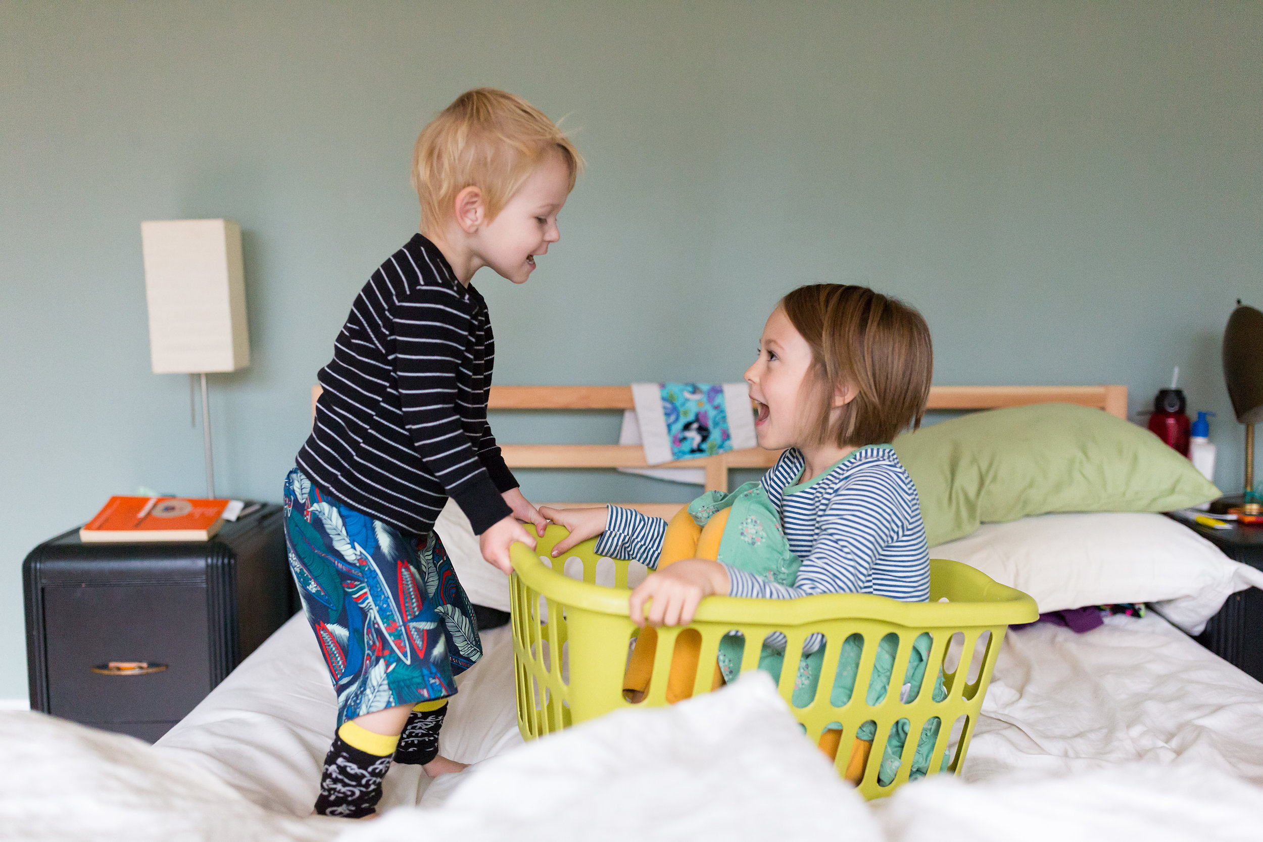 brother and sister play on bed in a laundry basket