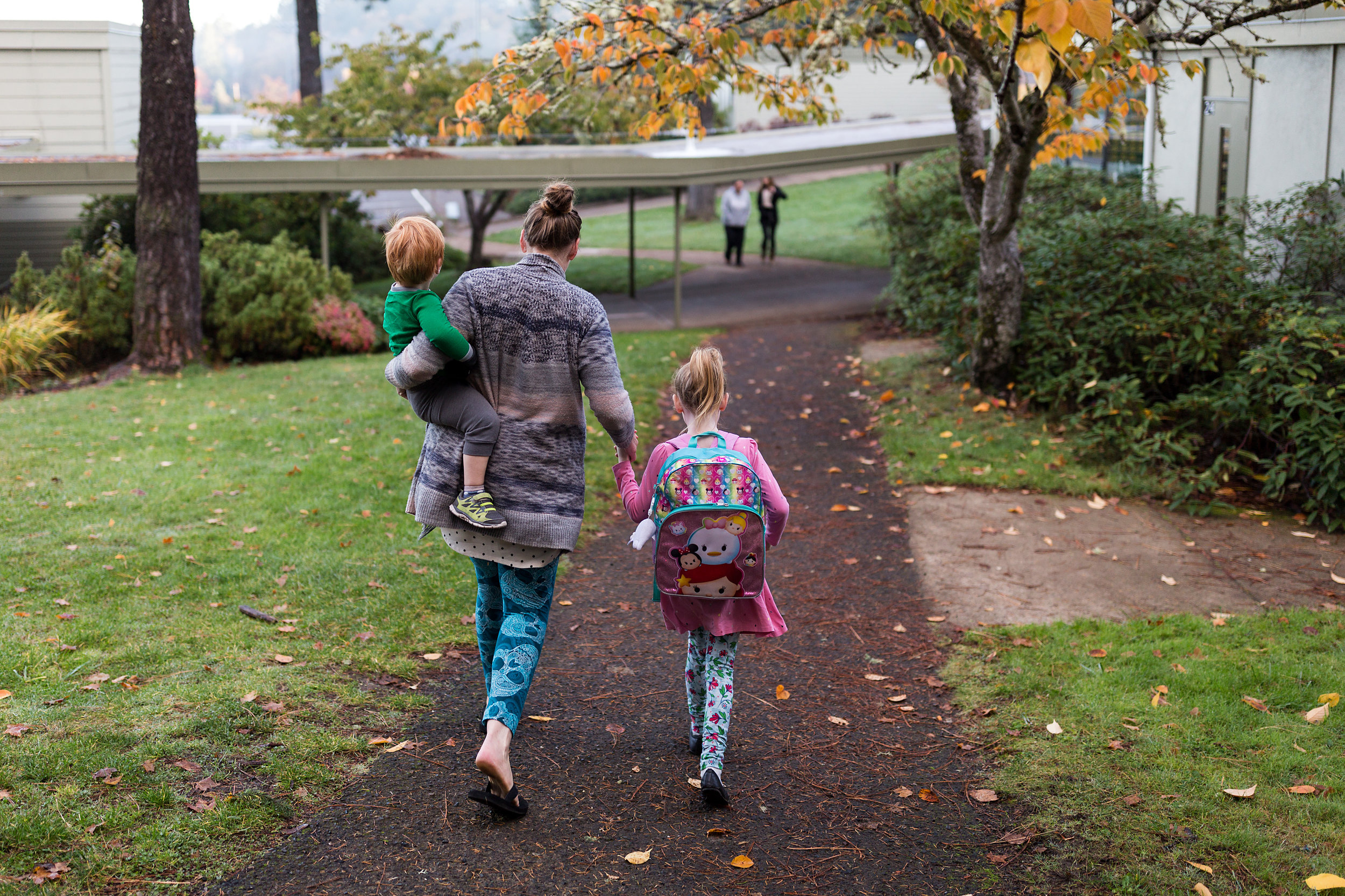 mom walks hand in hand with daughter to school